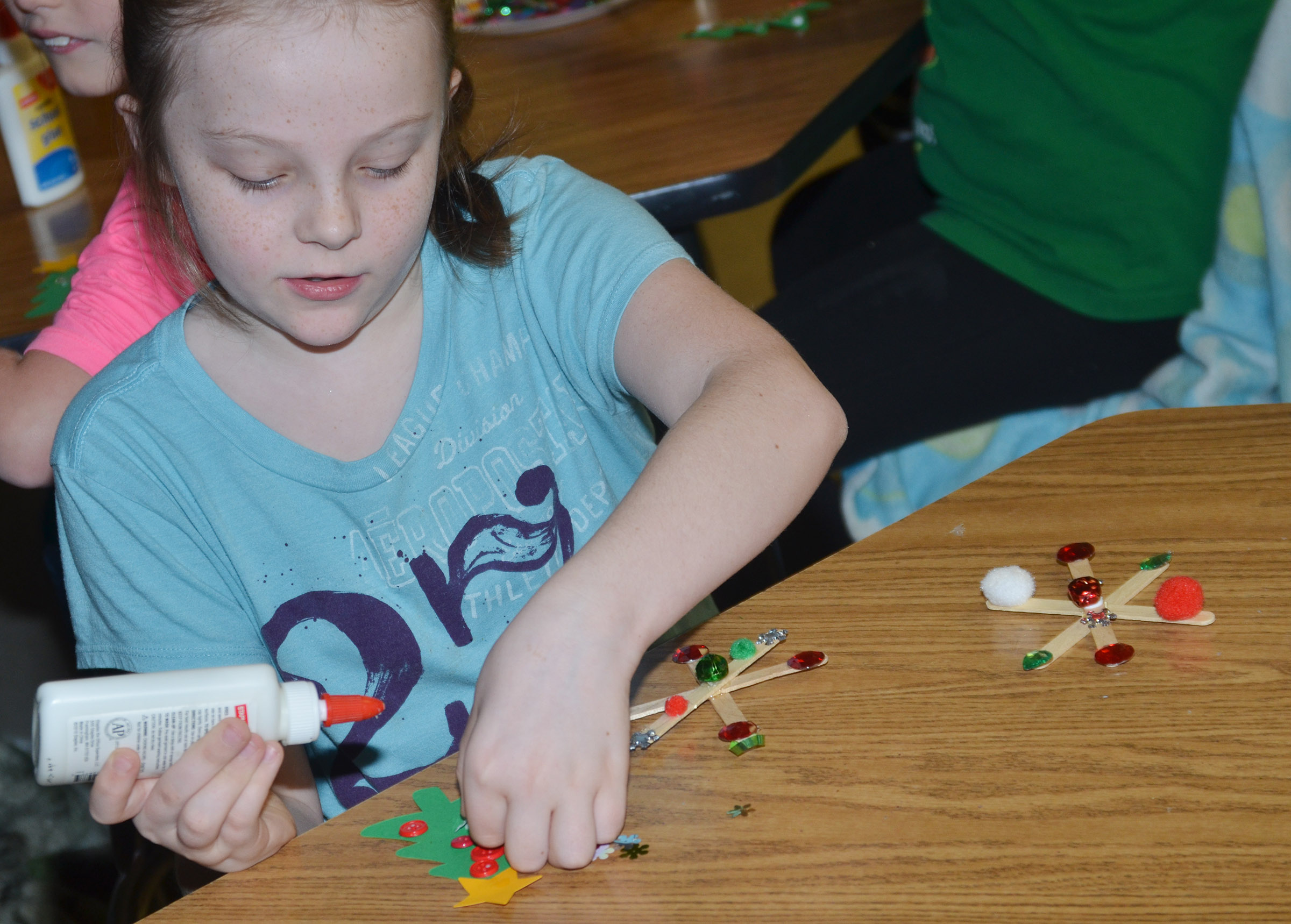 CES third-grader Jaylen Clark makes Christmas tree and snowflake ornaments.