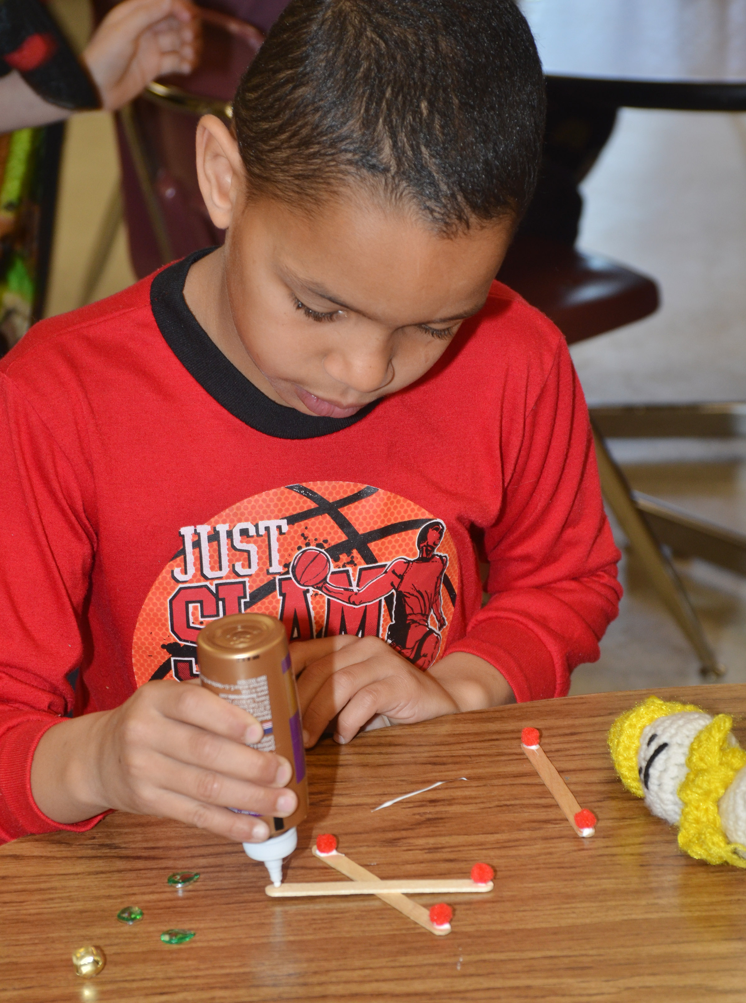 CES third-grader Anthony Goins makes a snowflake ornament.