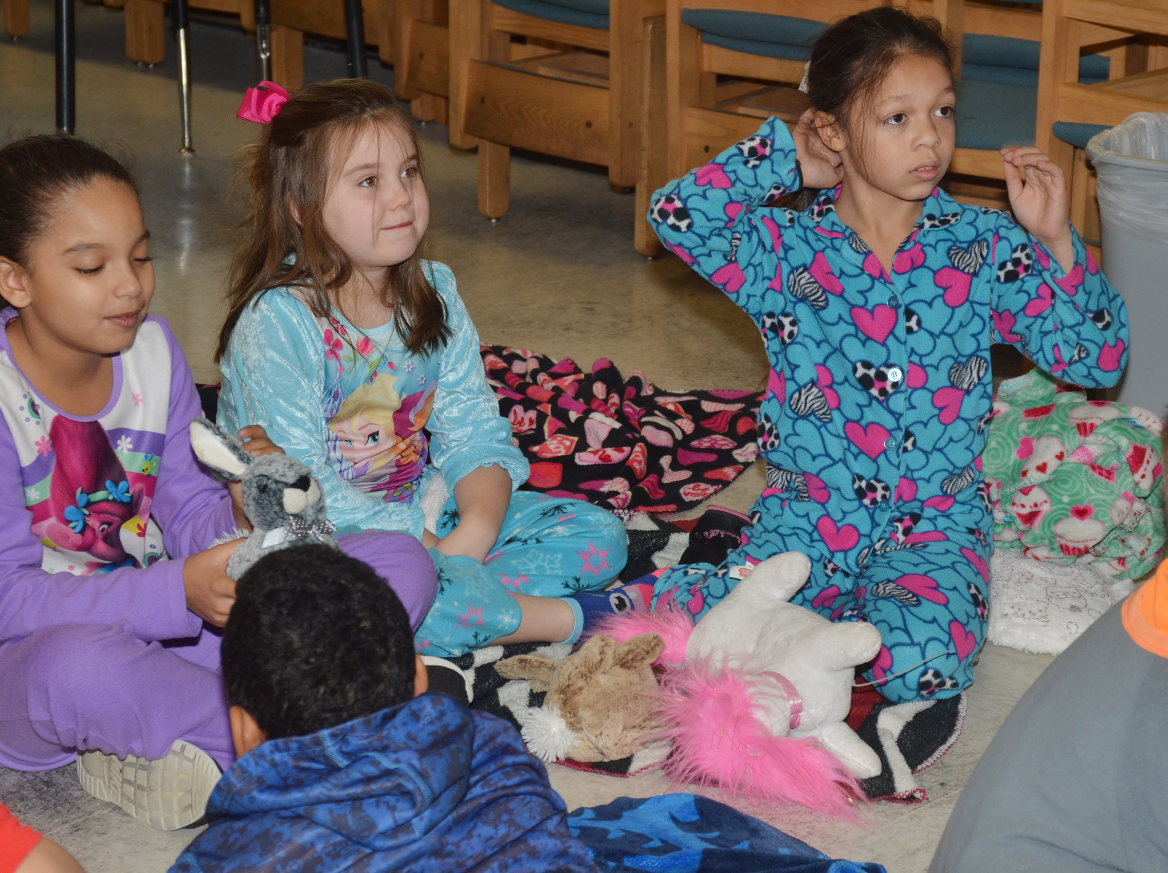 CES third-graders, from left, Aleecia Knezevic, Maylee Wilds and Breona Bridgewater sit together on their blankets as they watch a movie together.