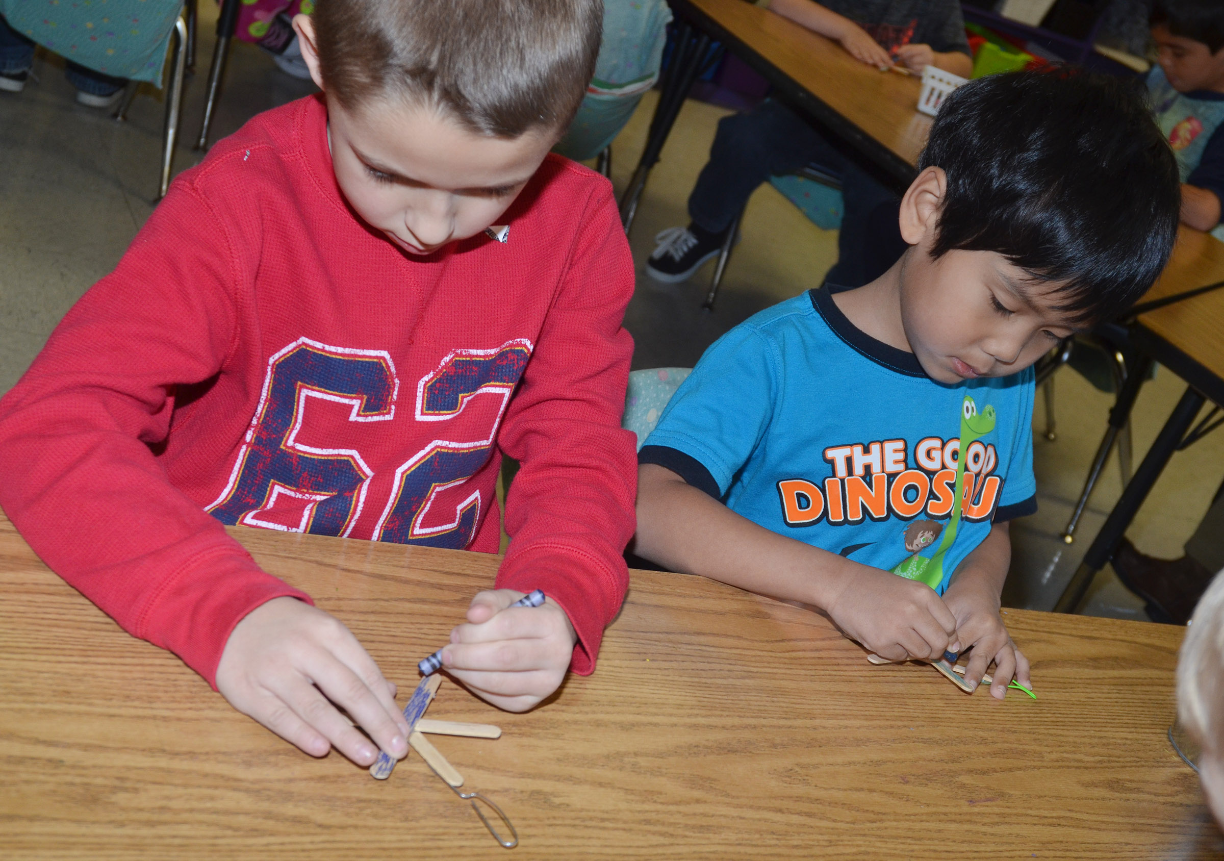 CES first-graders Aiden Forrest, at left, and Zach Hak color their snowflake ornaments before they add glitter to them.