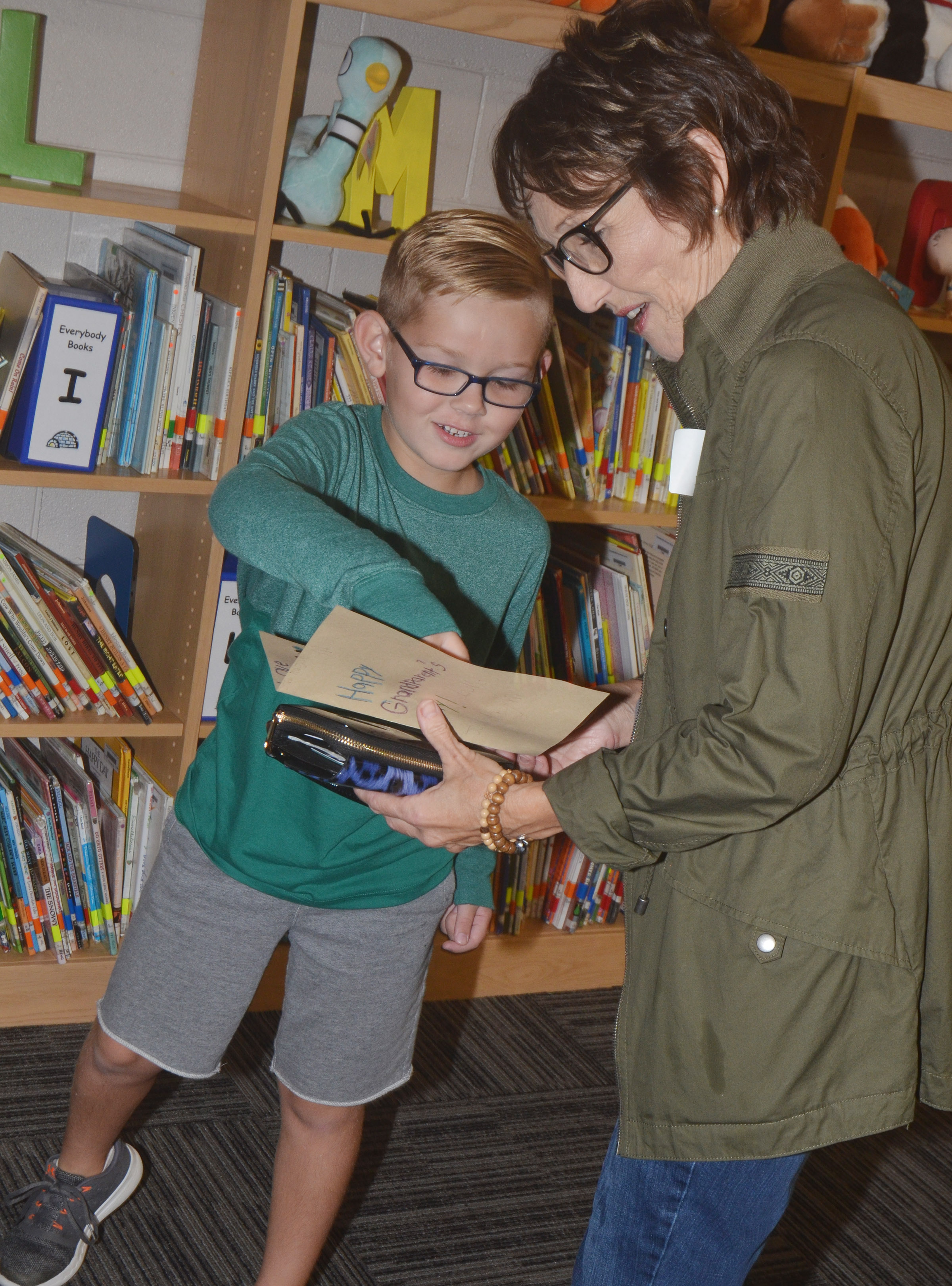 CES first-grader John Hagan Newton looks at a book with his grandmother.