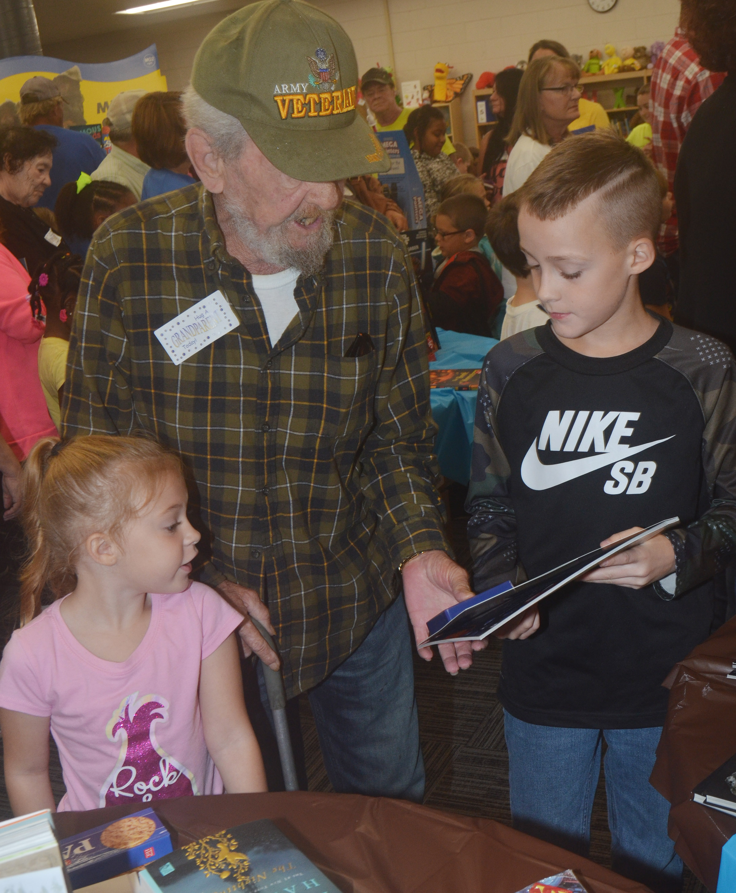 CES fourth-grader Caysen Tungate looks at a book with his grandfather and kindergartener Ava Caffee.