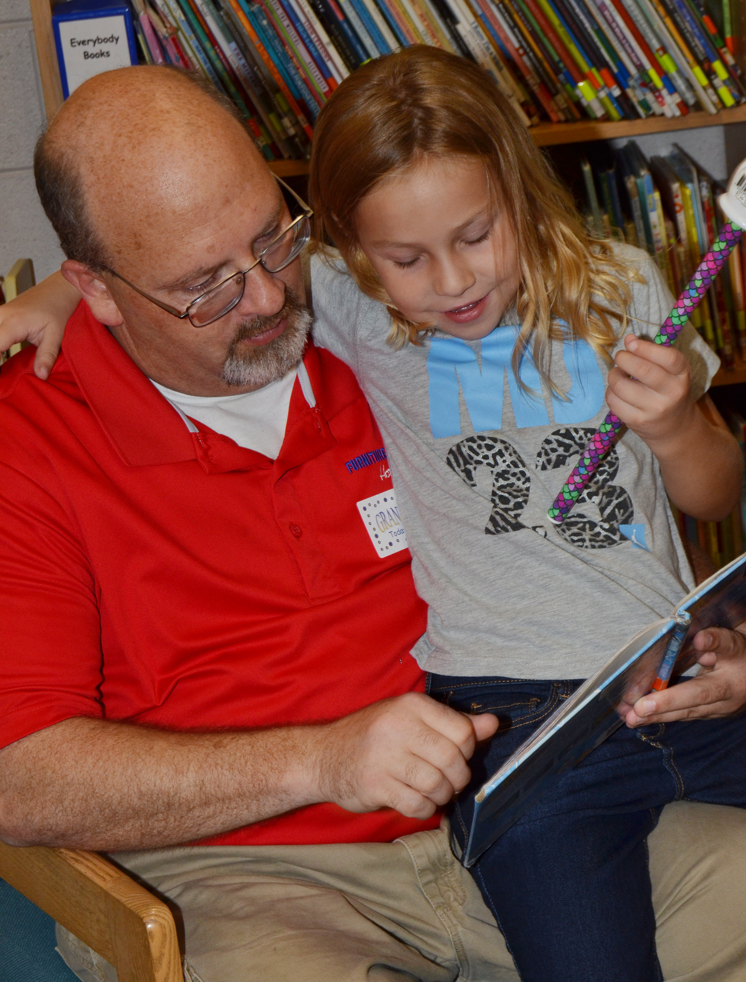 CES kindergartener Kira Dotson reads with her grandfather.