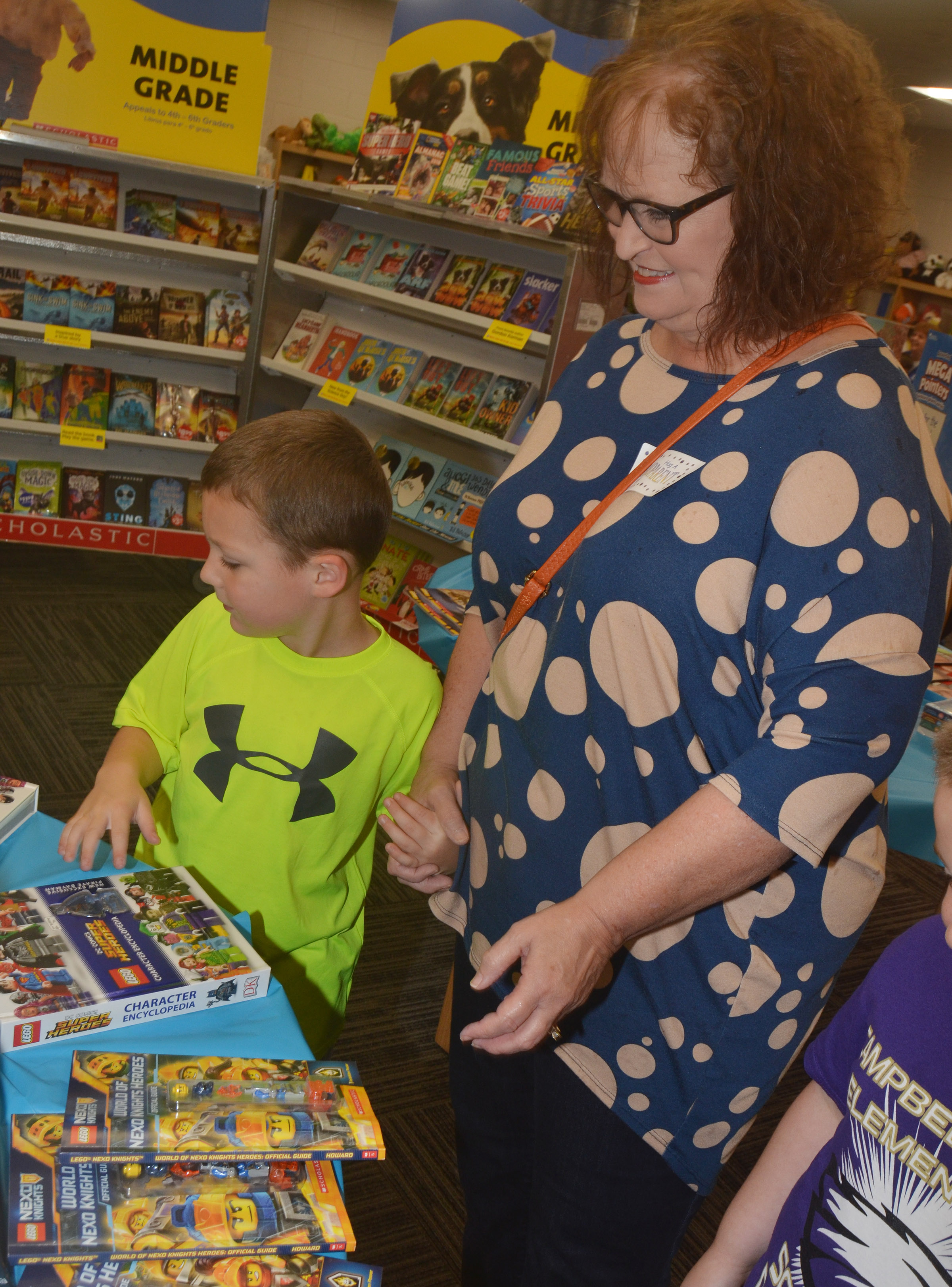 CES kindergartener Kyler Wilson looks at books with his grandmother.