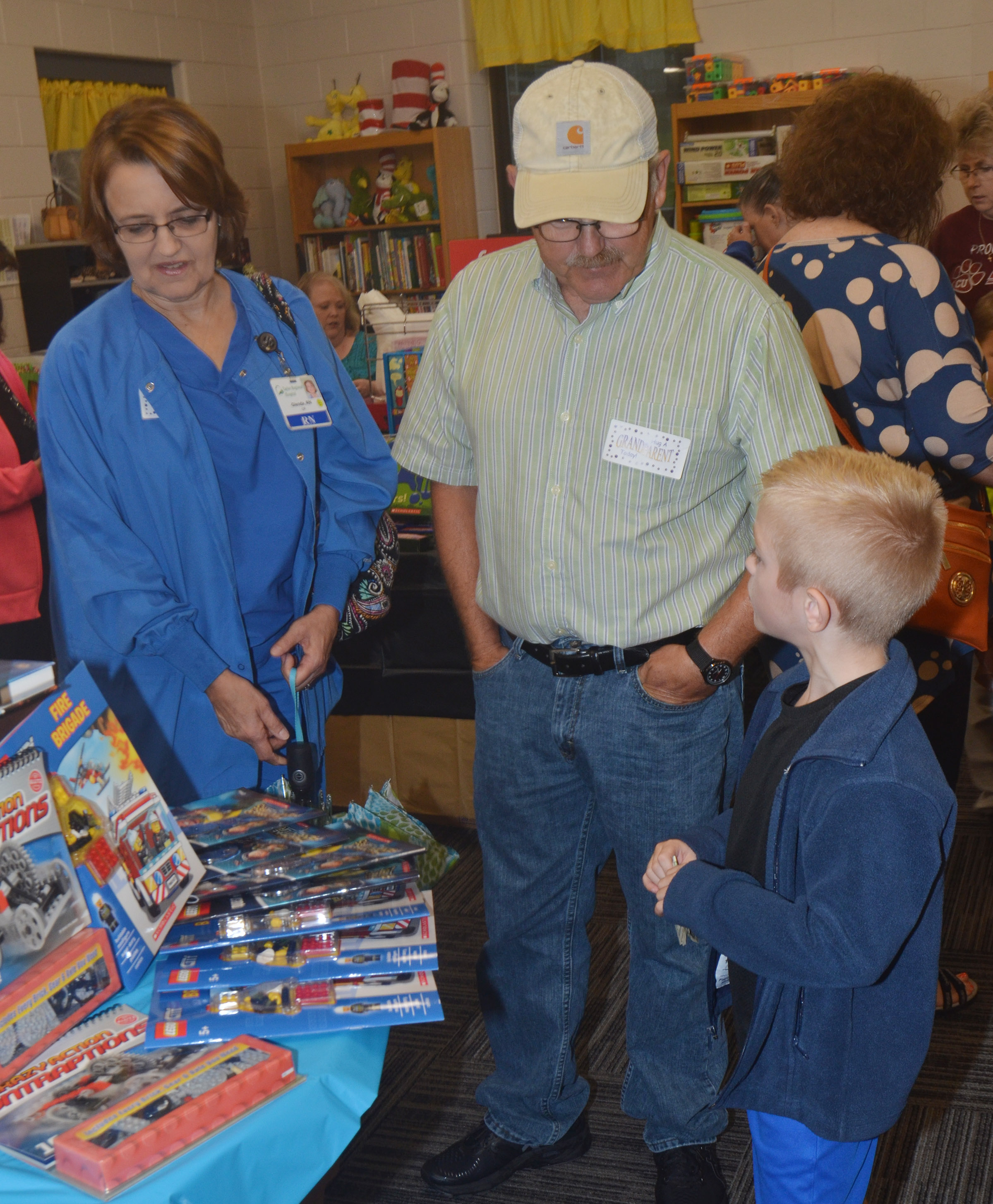 CES third-grader Evan Cundiff looks at books with his grandparents.