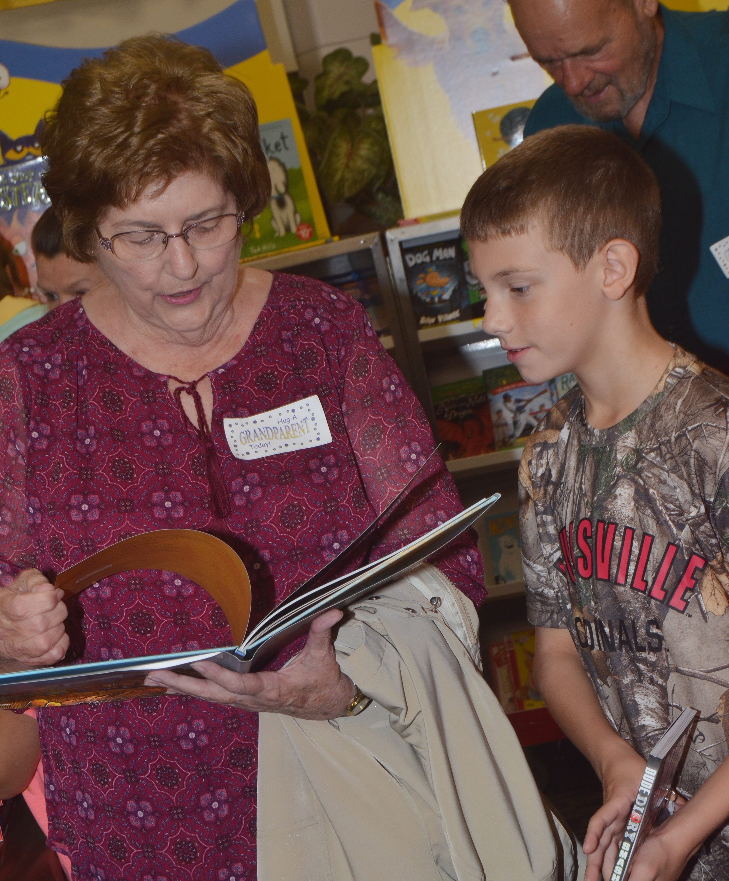 CES third-grader Aidan Wilson looks at books with his grandmother.