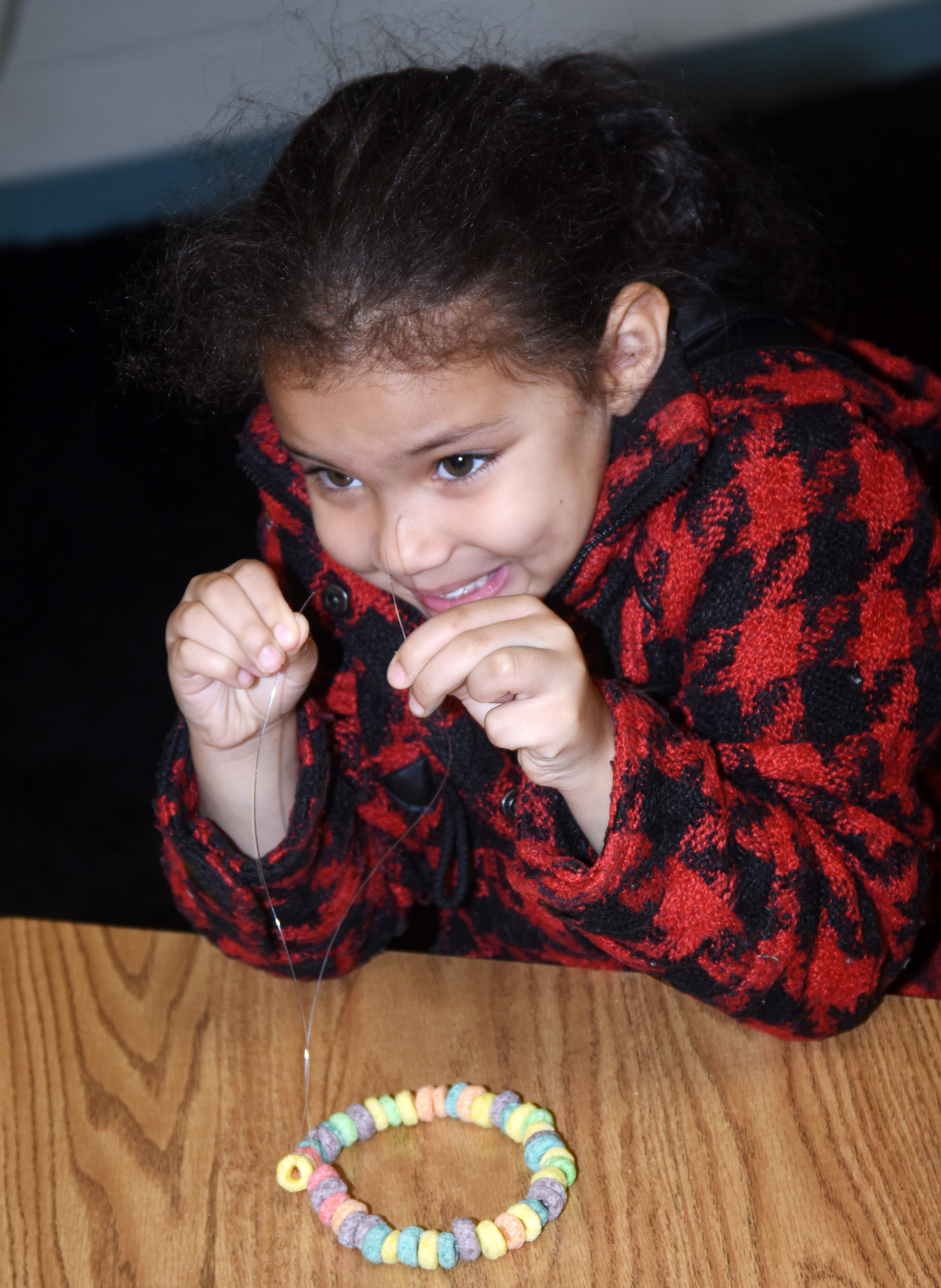 CES first-grader Jasymon Musselwhite counts pieces of cereal as she makes her necklace.