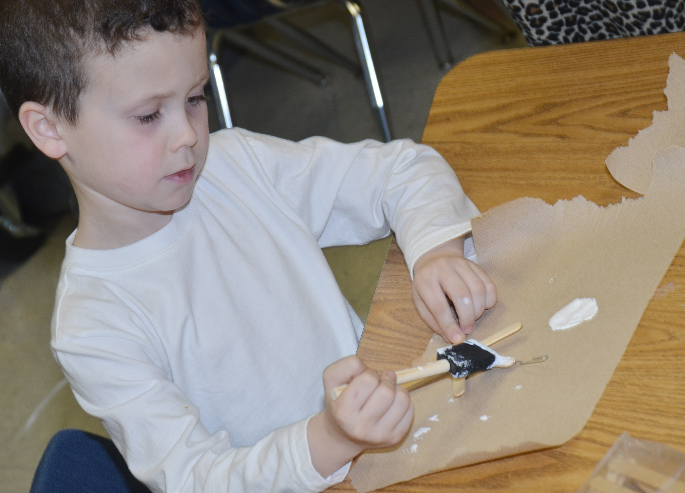 CES second-grader Braydan Dyer paints his snowflake ornament.