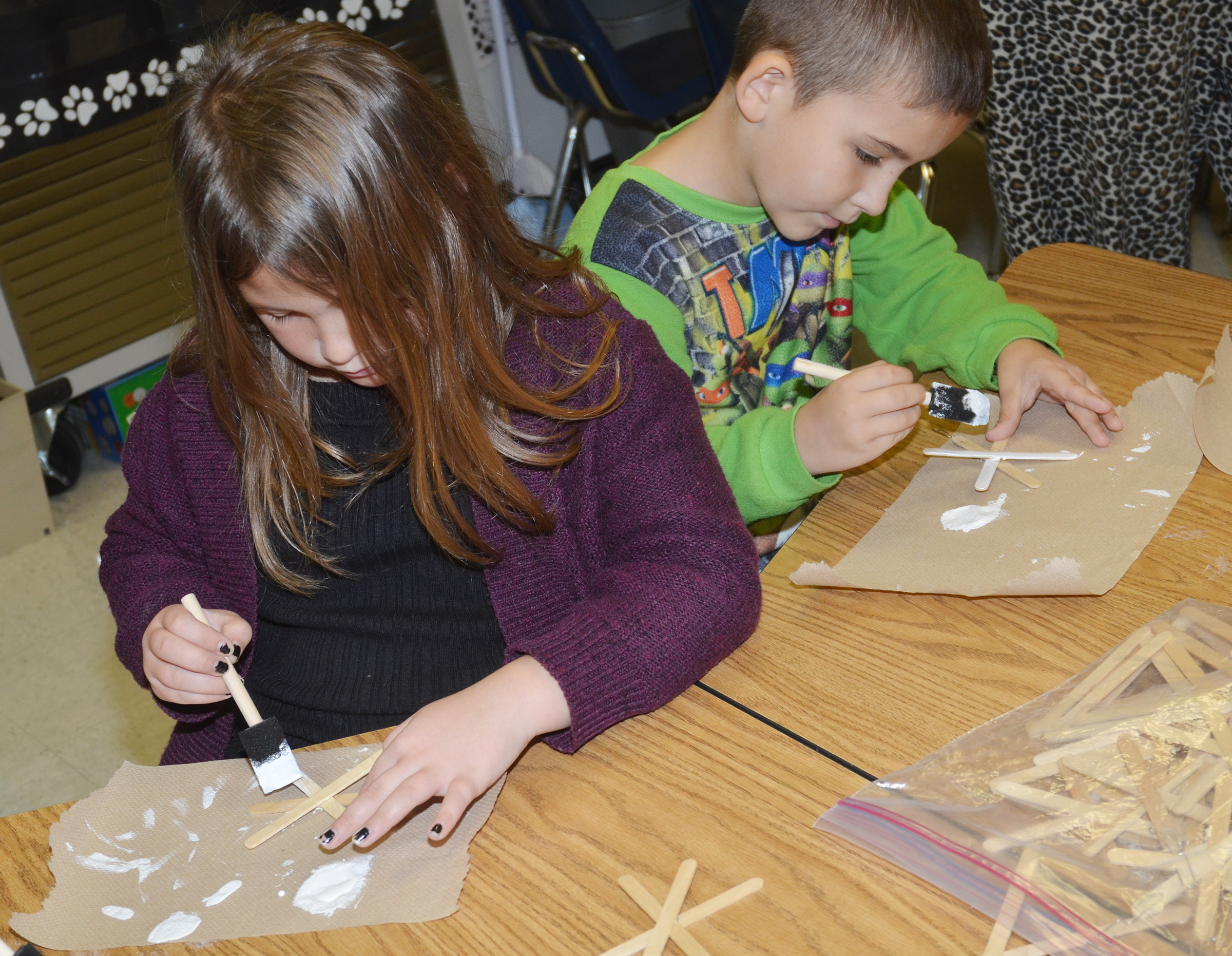 CES second-graders Destiny Rhinehart, at left, and Josiah Edwards paint their snowflake ornaments.