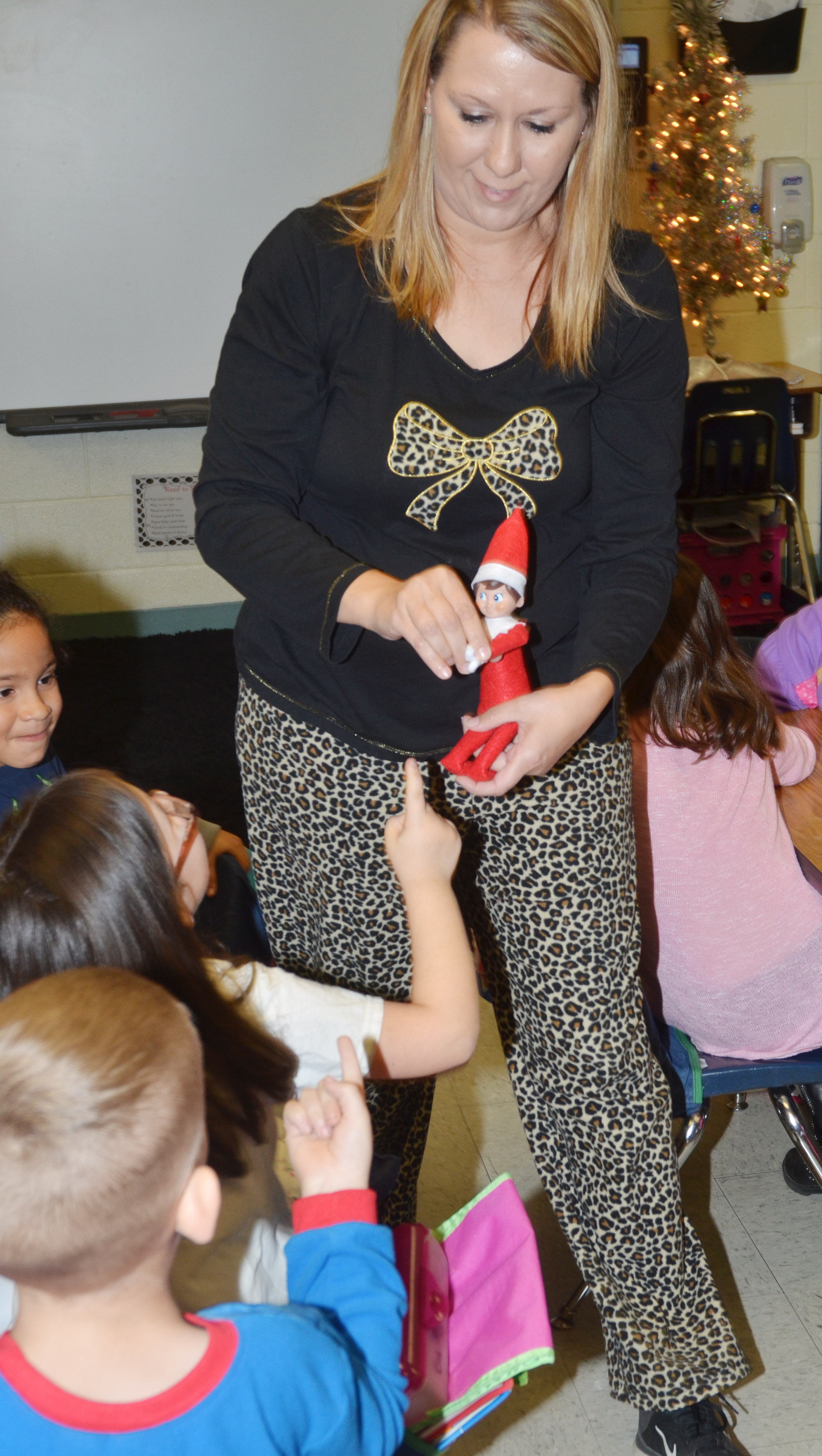 CES second-grade teacher Amanda Greer introduces the class elf to Trinity Clark.