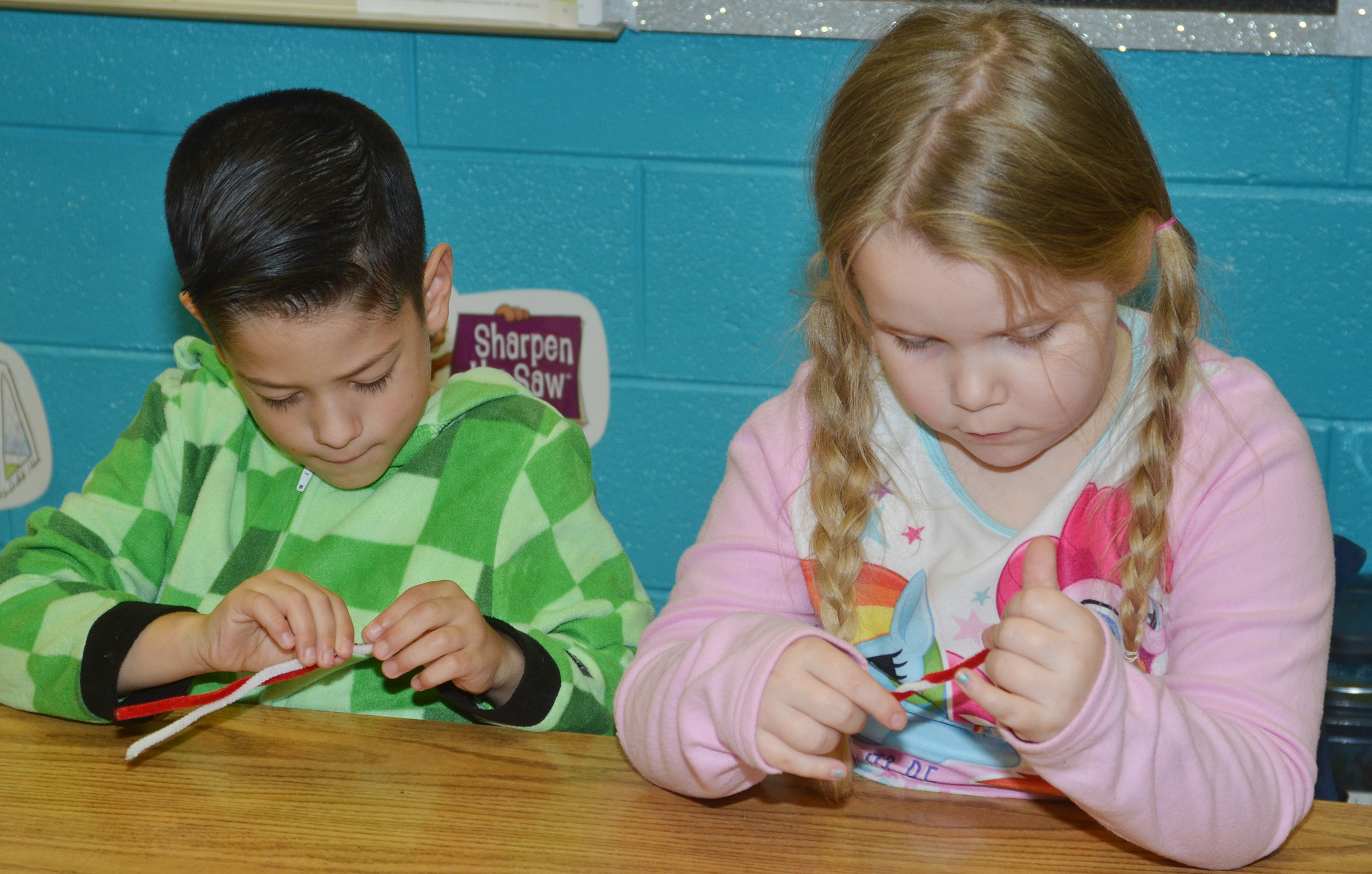CES second-graders Abram Adkins, at left, and Cera Rooker make their candy cane ornaments.