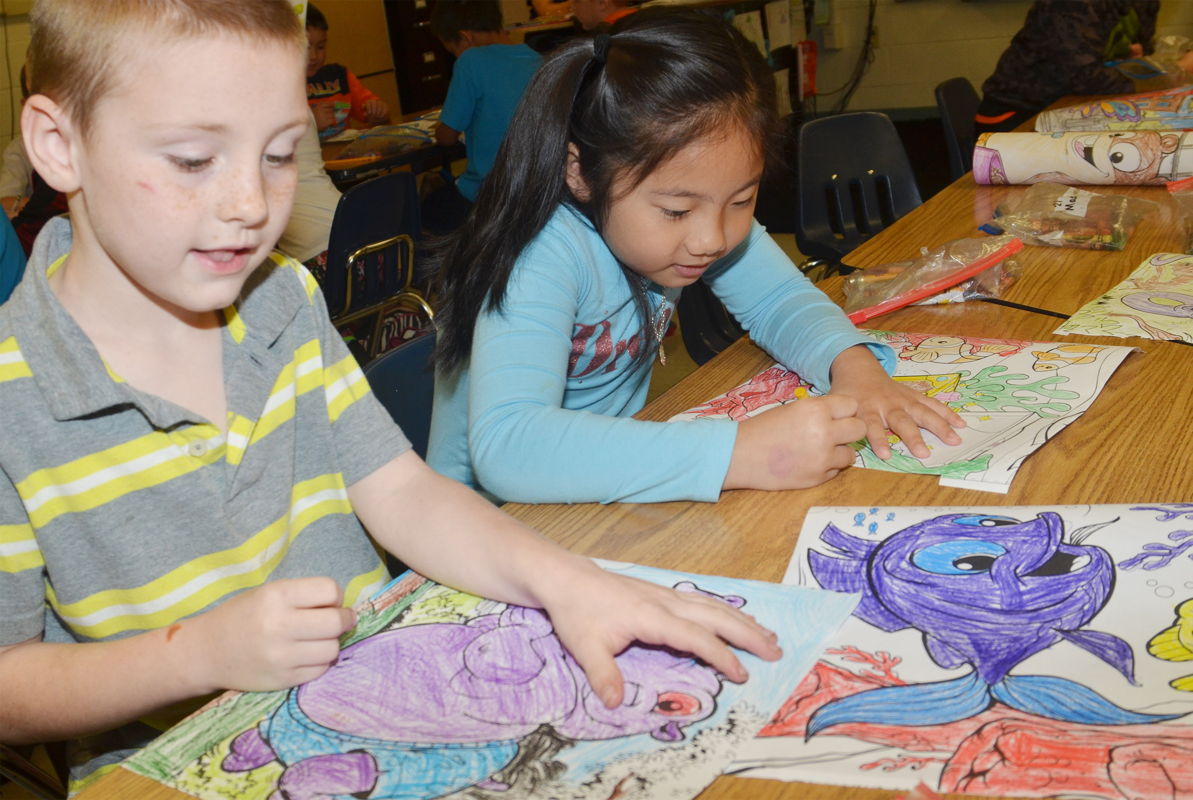 CES first-graders James Brunner, at left, and Tina Jiang color.