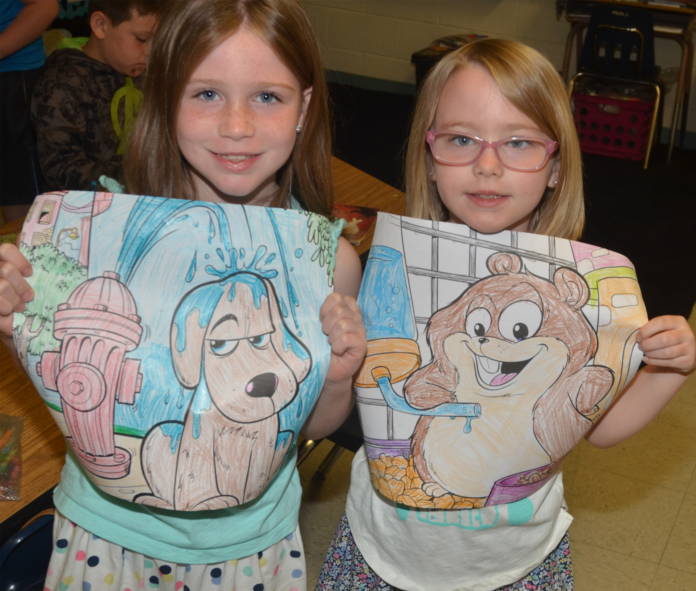 CES first-graders Izzy Brunelle, at left, and her sister Maddie hold their coloring pictures.