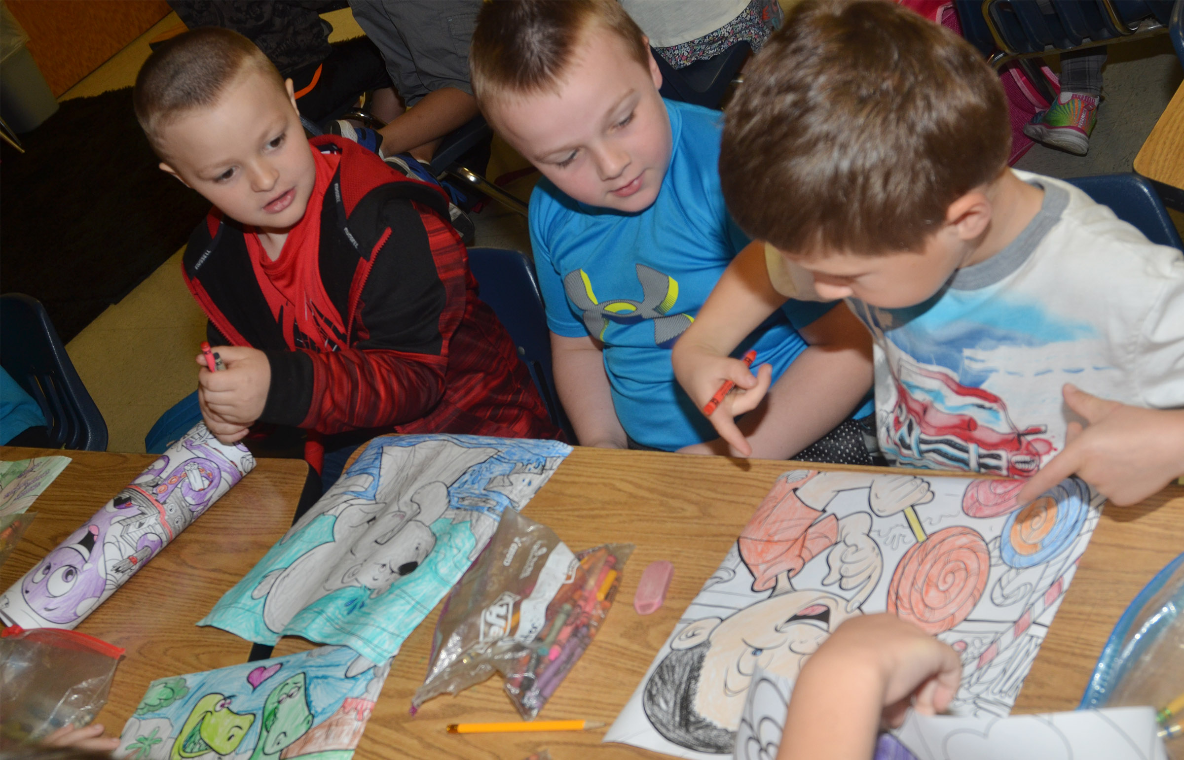From left, CES first-graders Caleb Ortiz, Hunter Clark and Bryson Gabehart talk about their coloring pictures.