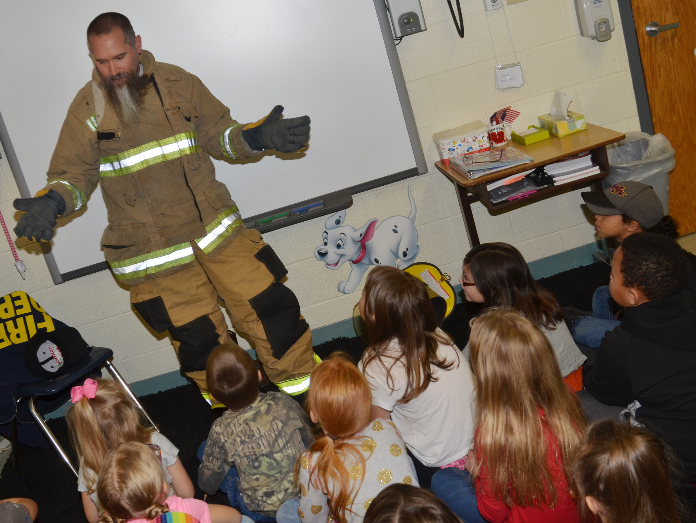 Randy Bricken, who is a volunteer firefighter at Taylor County Fire & Rescue and a custodial worker at Campbellsville elementary, middle and high schools, talks to CES first-graders about his job as a firefighter and the equipment he uses to keep him safe.