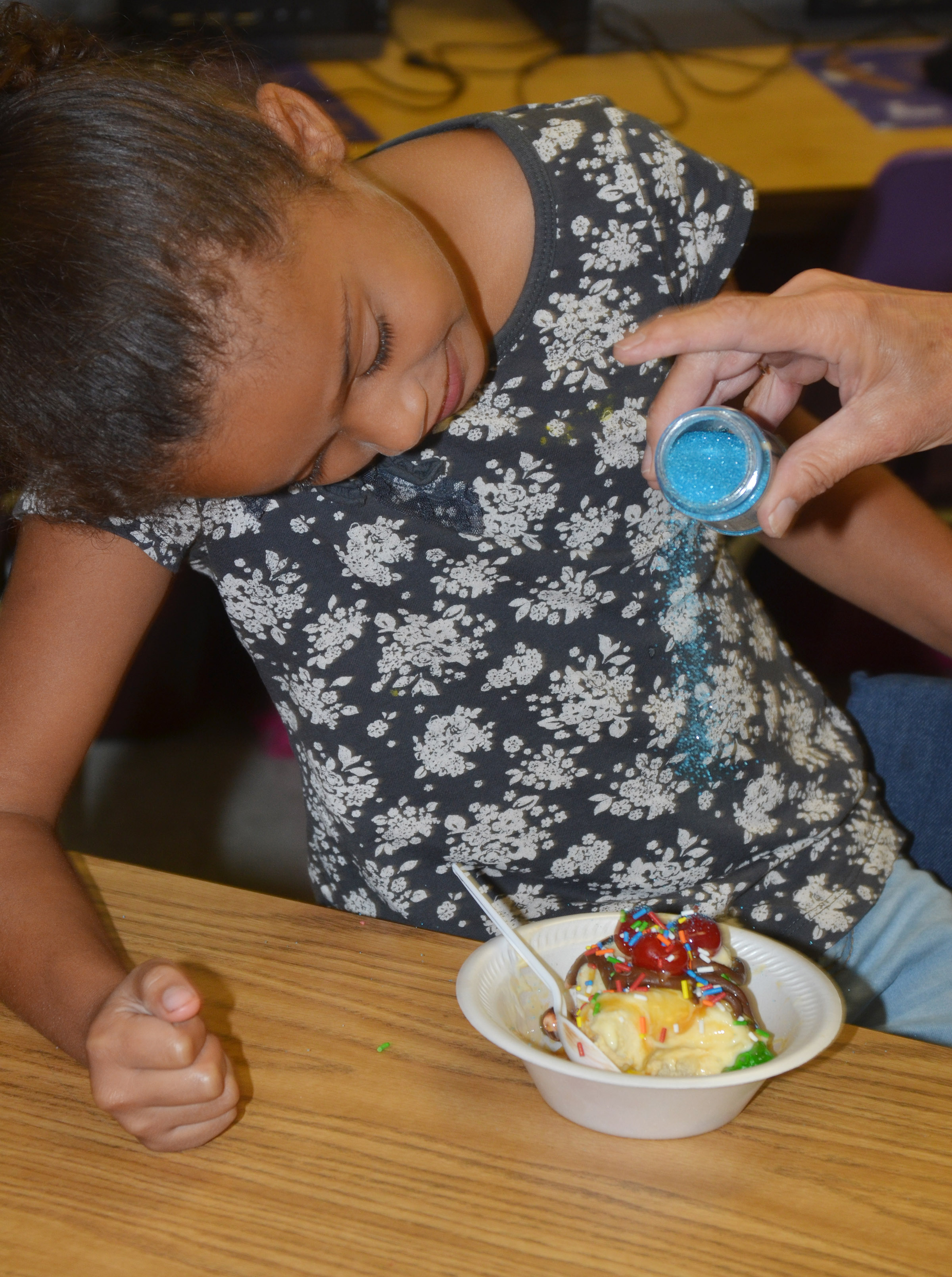 CES first-grader Jyra Welch watches as sprinkles are the finishing touch on her ice cream sundae.