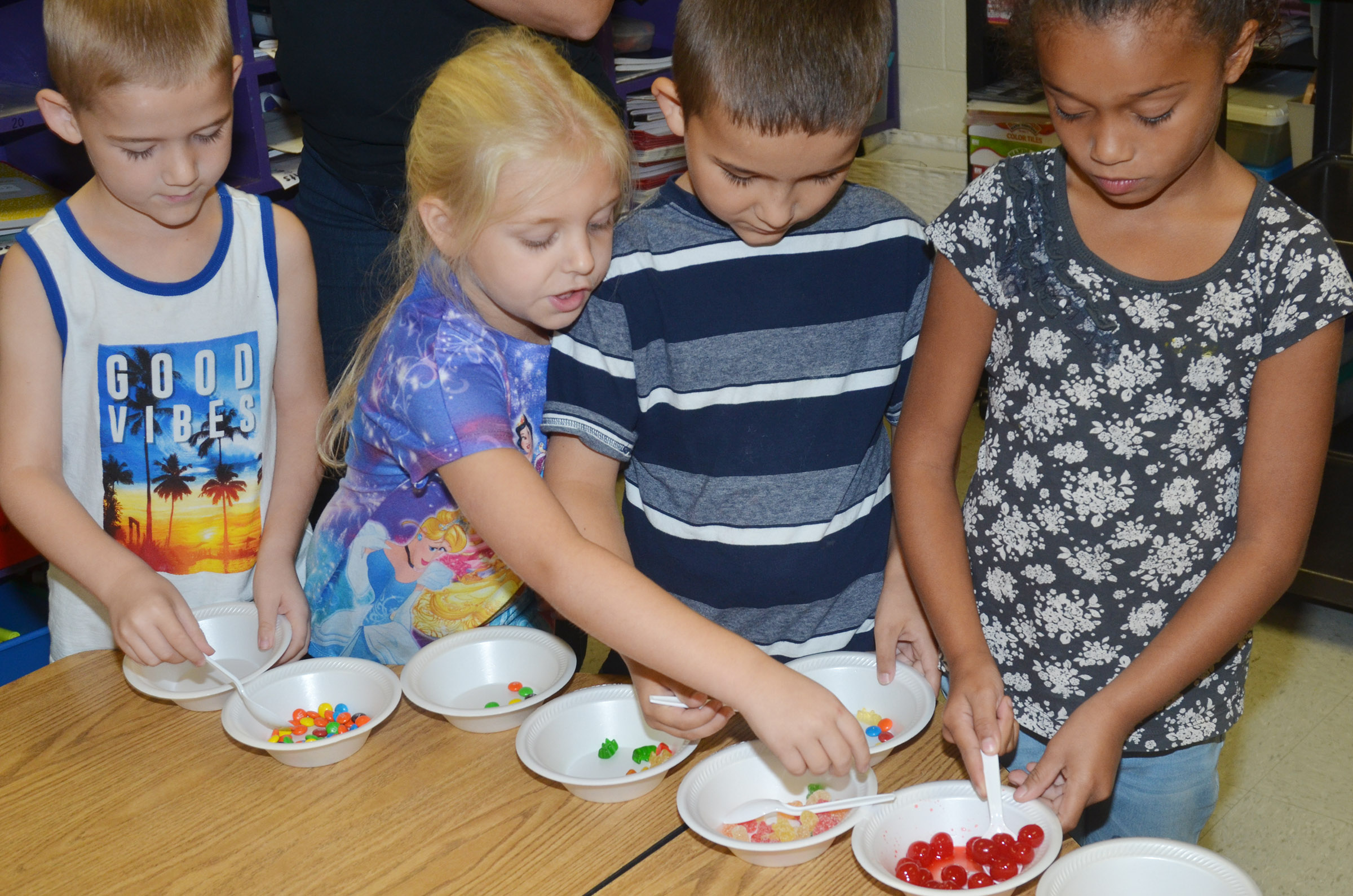 CES first-graders, from left, Mason Edwards, Aubrey Novak, Josiah Edwards and Jyra Welch get toppings for their ice cream sundaes.