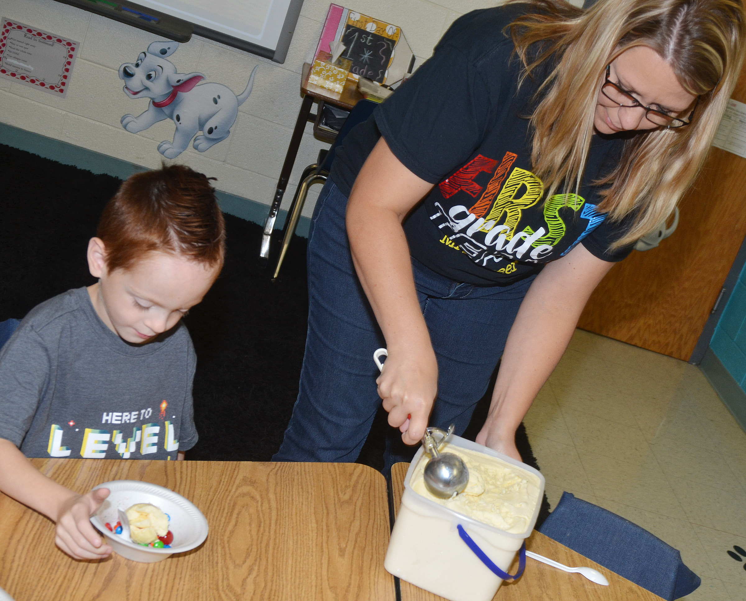 CES teacher Amanda Greer serves first-grader Carson Montes a scoop of ice cream.