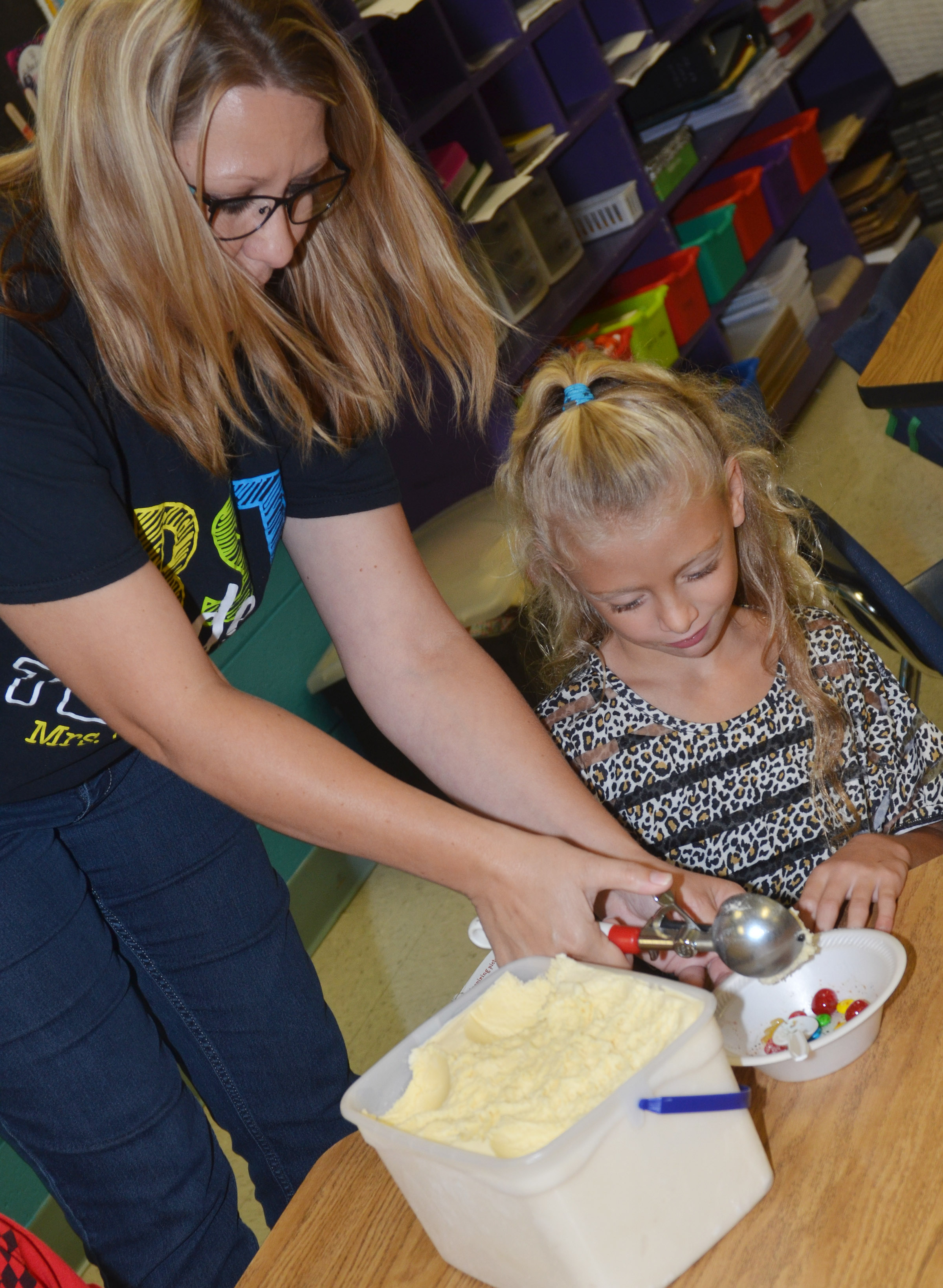 CES teacher Amanda Greer serves first-grader Aliyah Litsey a scoop of ice cream.
