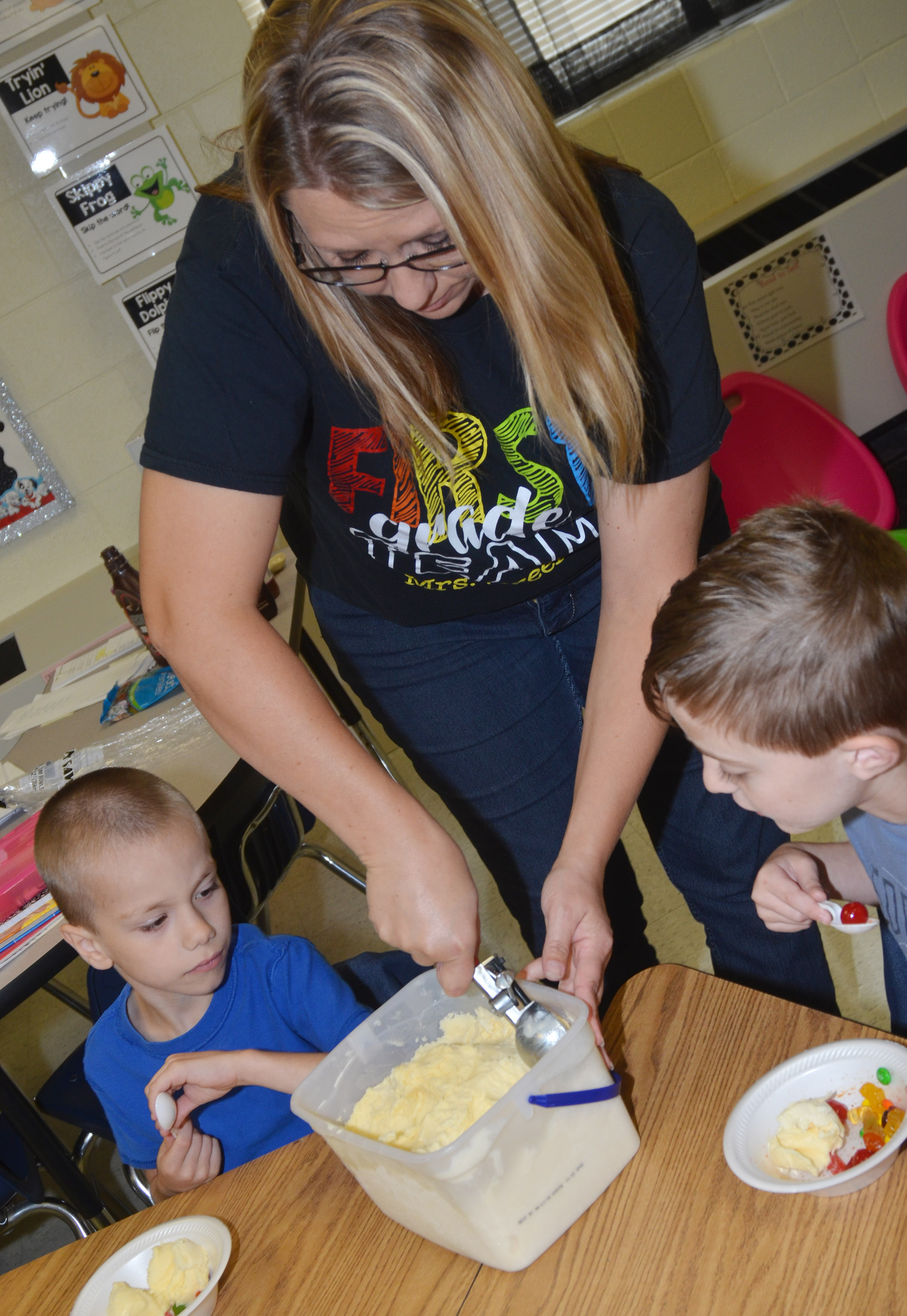CES teacher Amanda Greer serves first-graders Alex Eggers, at left, and Caleb Goodson ice cream.