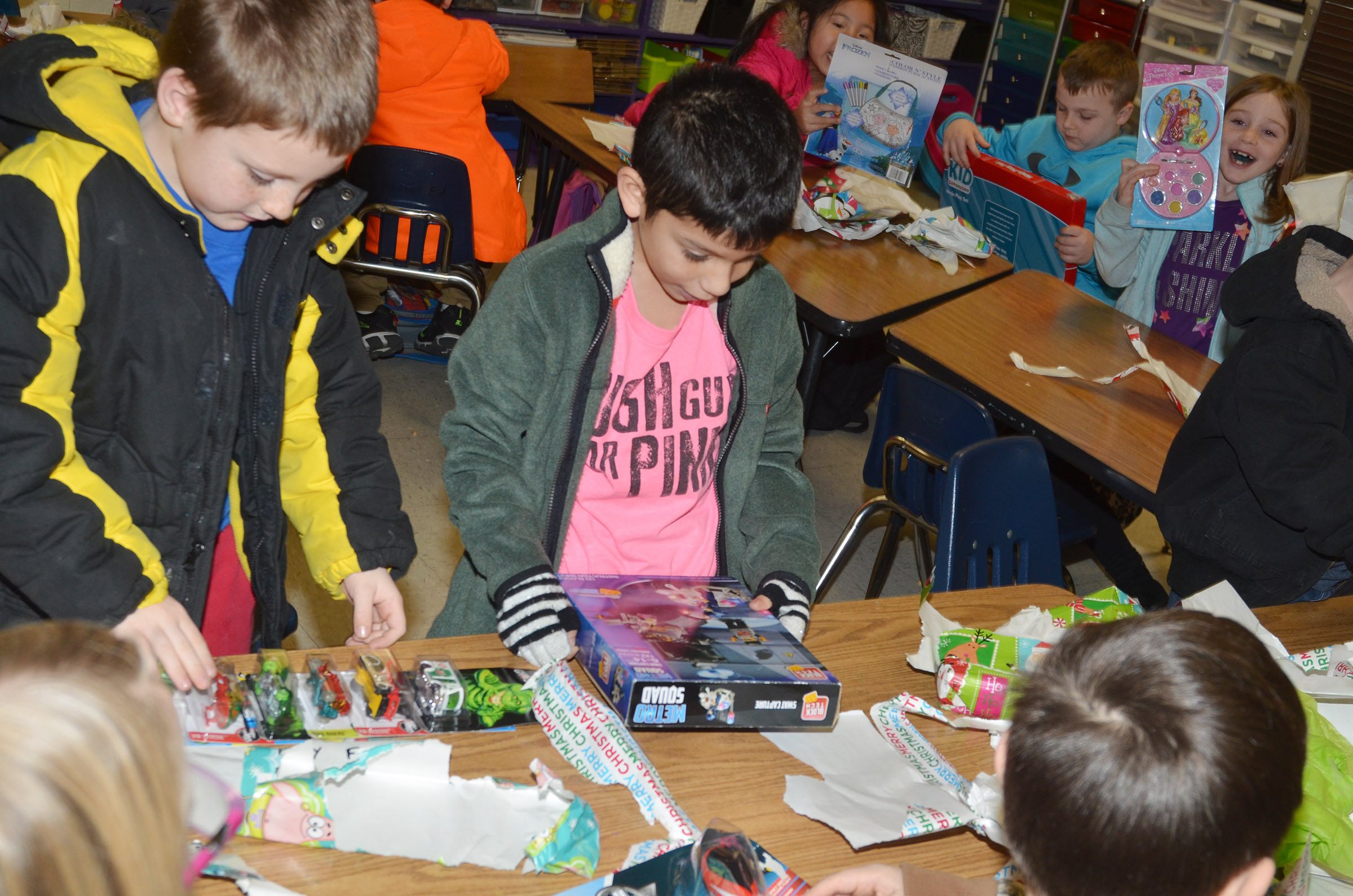 CES first-graders James Brunner, at left, and Trey Guajardo open their gifts in their gift exchange.
