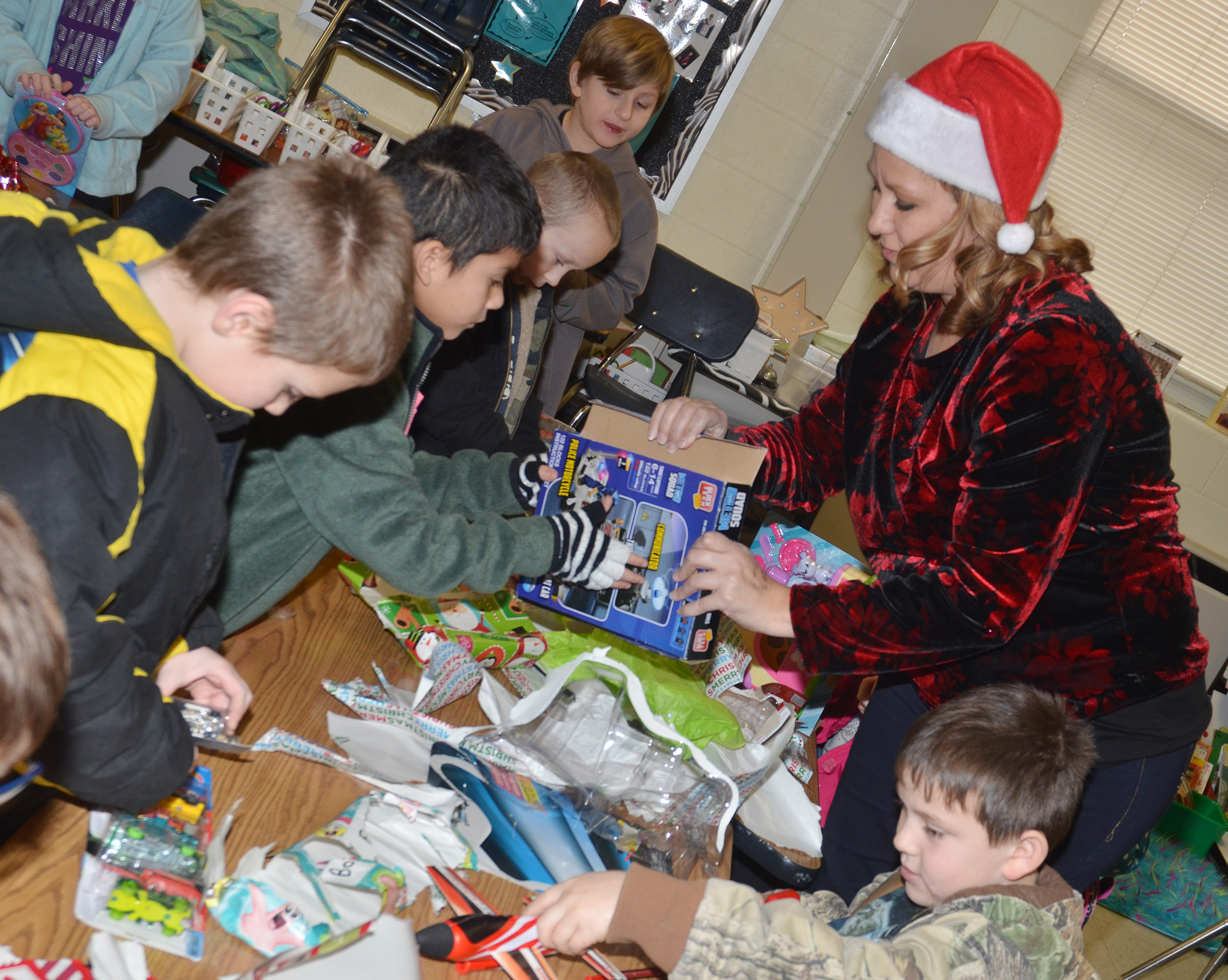 CES first-grade teacher Amanda Greer helps her students open their gifts during the class gift exchange.