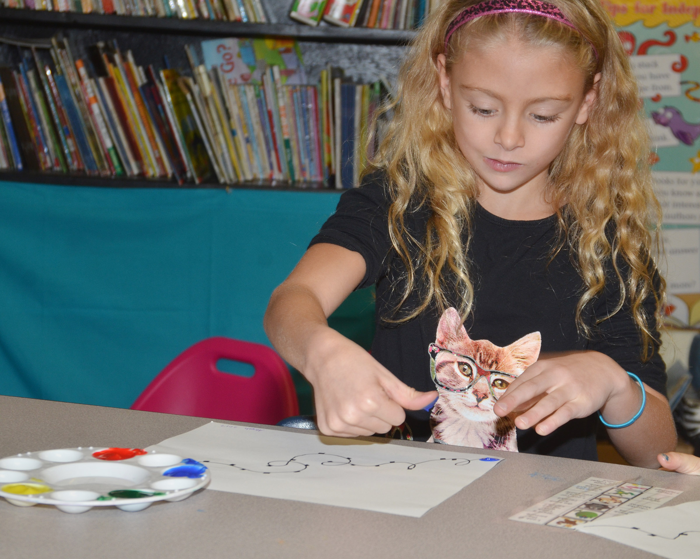 CES first-grader Aliyah Litsey paints her Christmas lights.