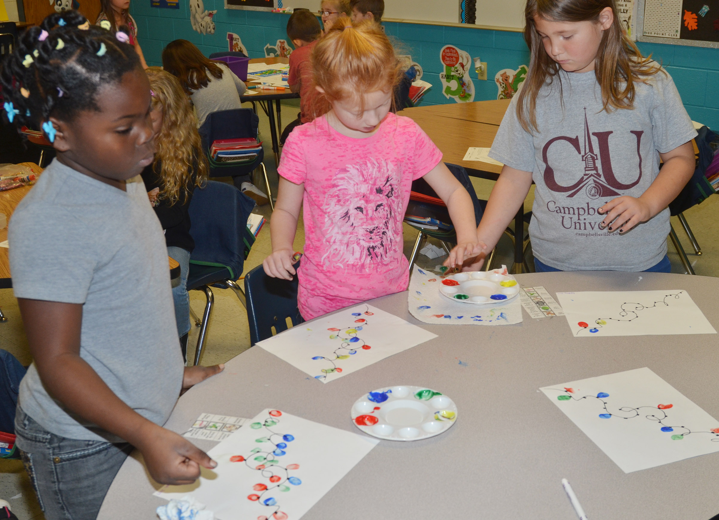From left, CES first-graders Aniyah Adams, Bella Stout and Destiny Rhinehart paint their Christmas lights.