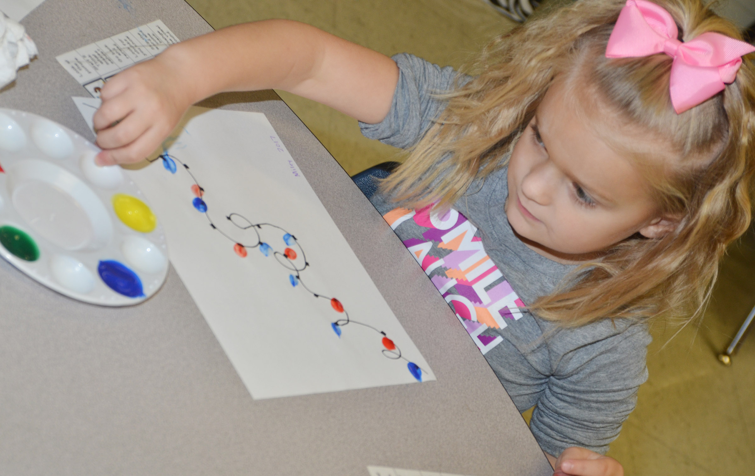 CES first-grader Miley Orberson paints her Christmas lights.