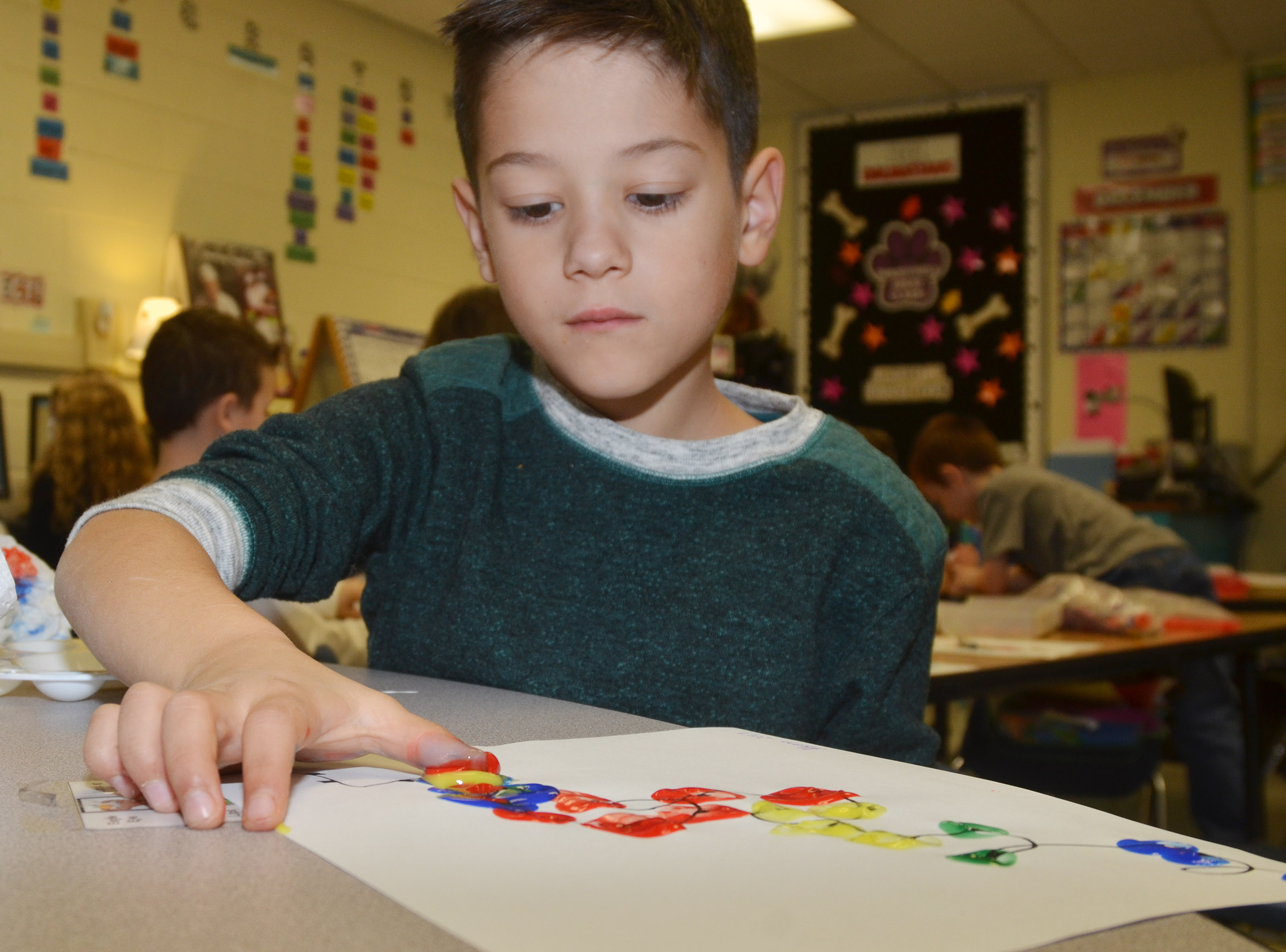 CES first-grader Abram Adkins paints his Christmas lights.