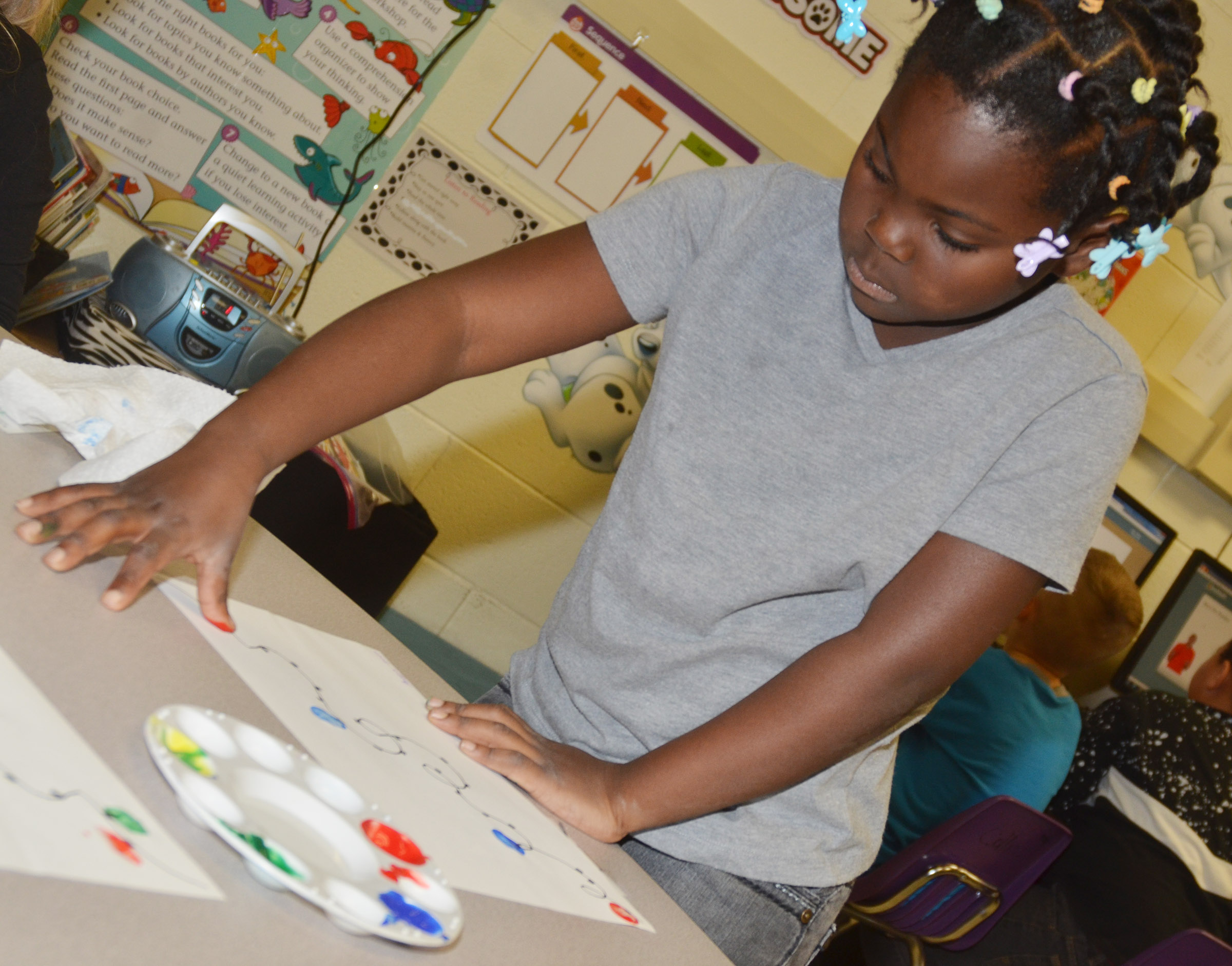 CES first-grader Aniyah Adams paints her Christmas lights.
