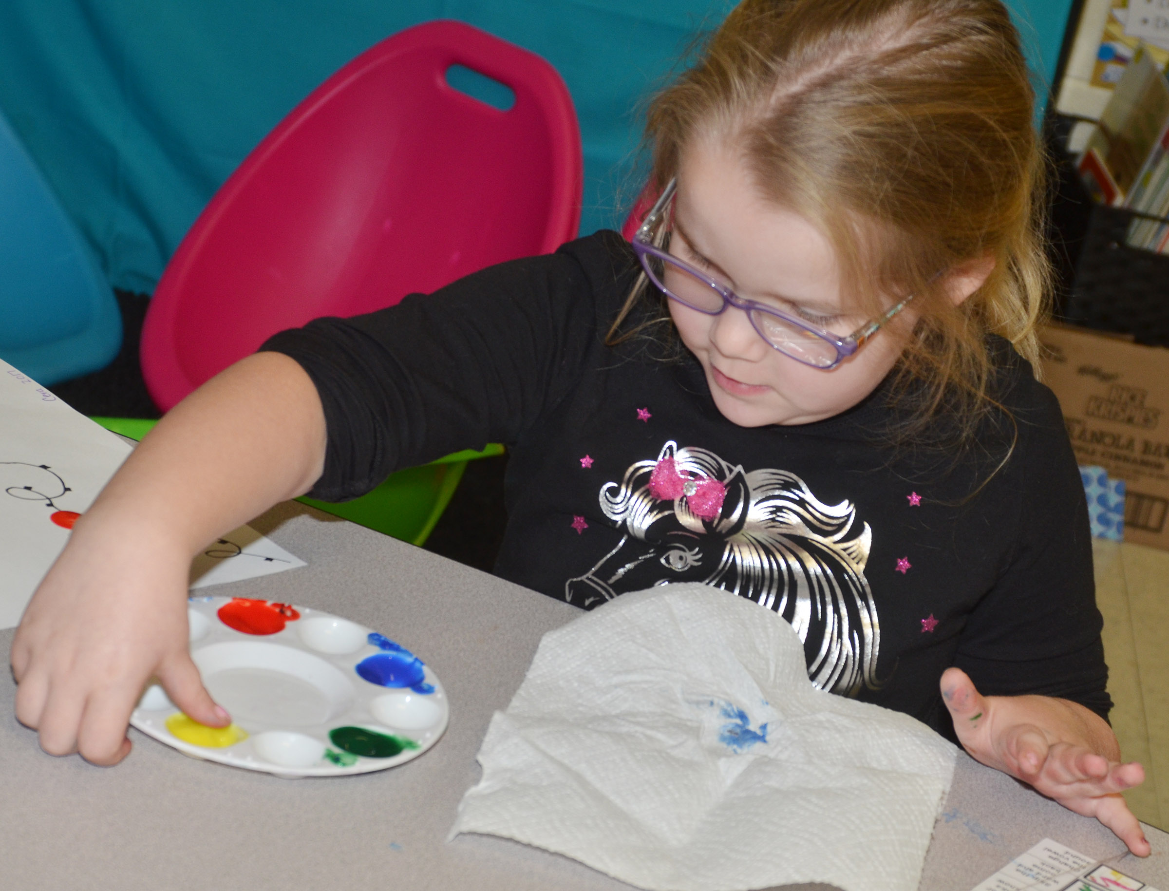 CES first-grader Cera Rooker paints her Christmas lights.