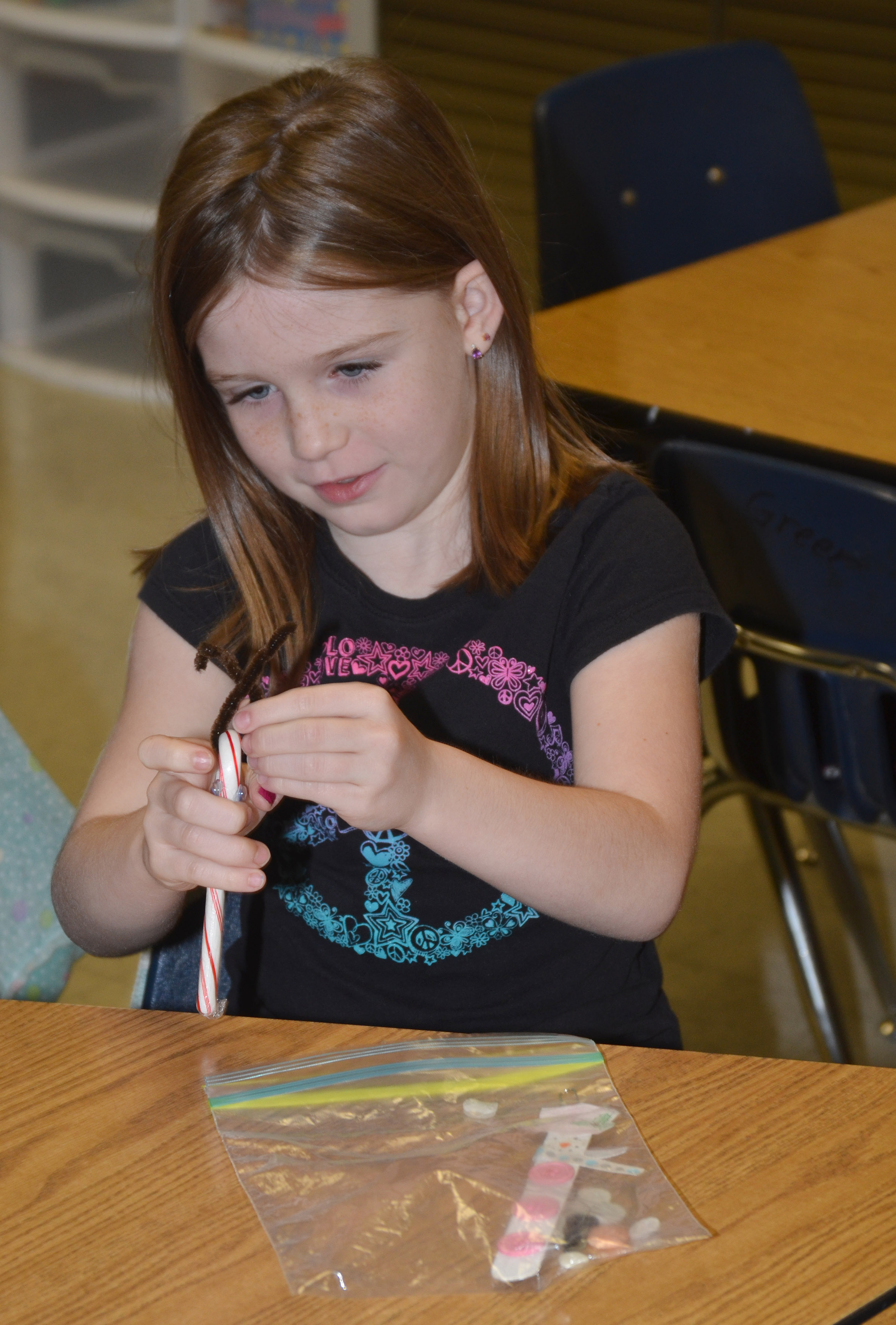 CES first-grader Isabella Brunelle adds antlers to her candy cane ornament.