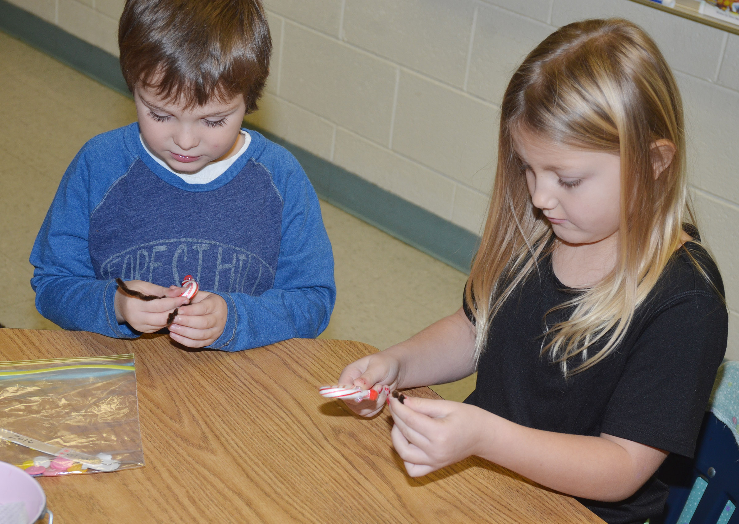 CES first-graders Karson Burchett, at left, and Asia Singleton add antlers to their candy cane ornaments.