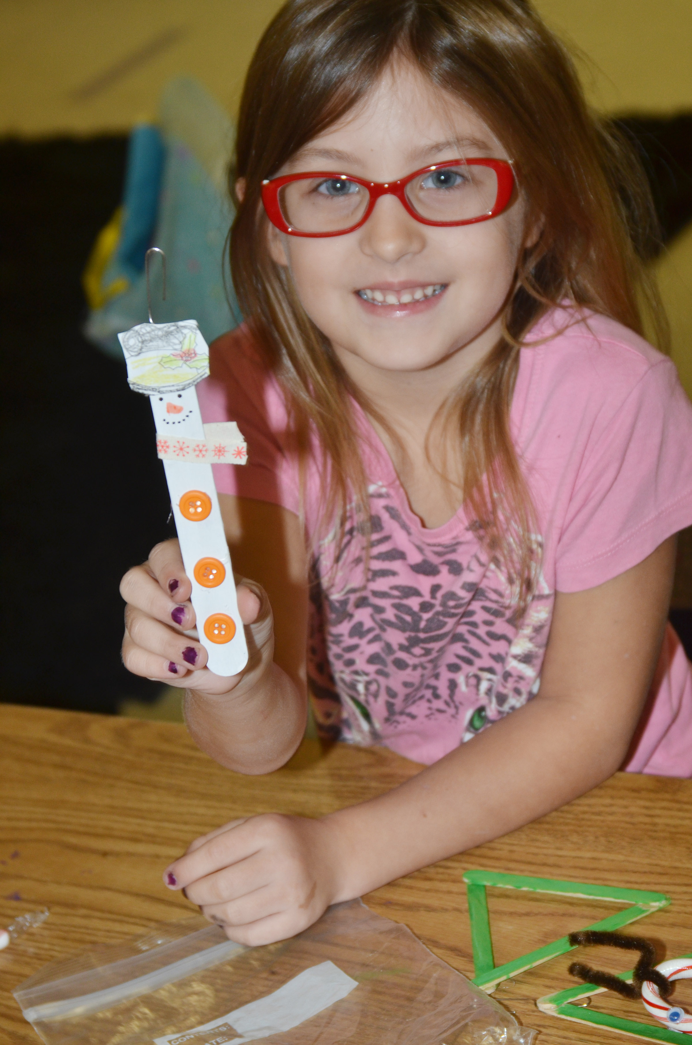 CES first-grader Alexis Mann holds her finished snowman ornament.