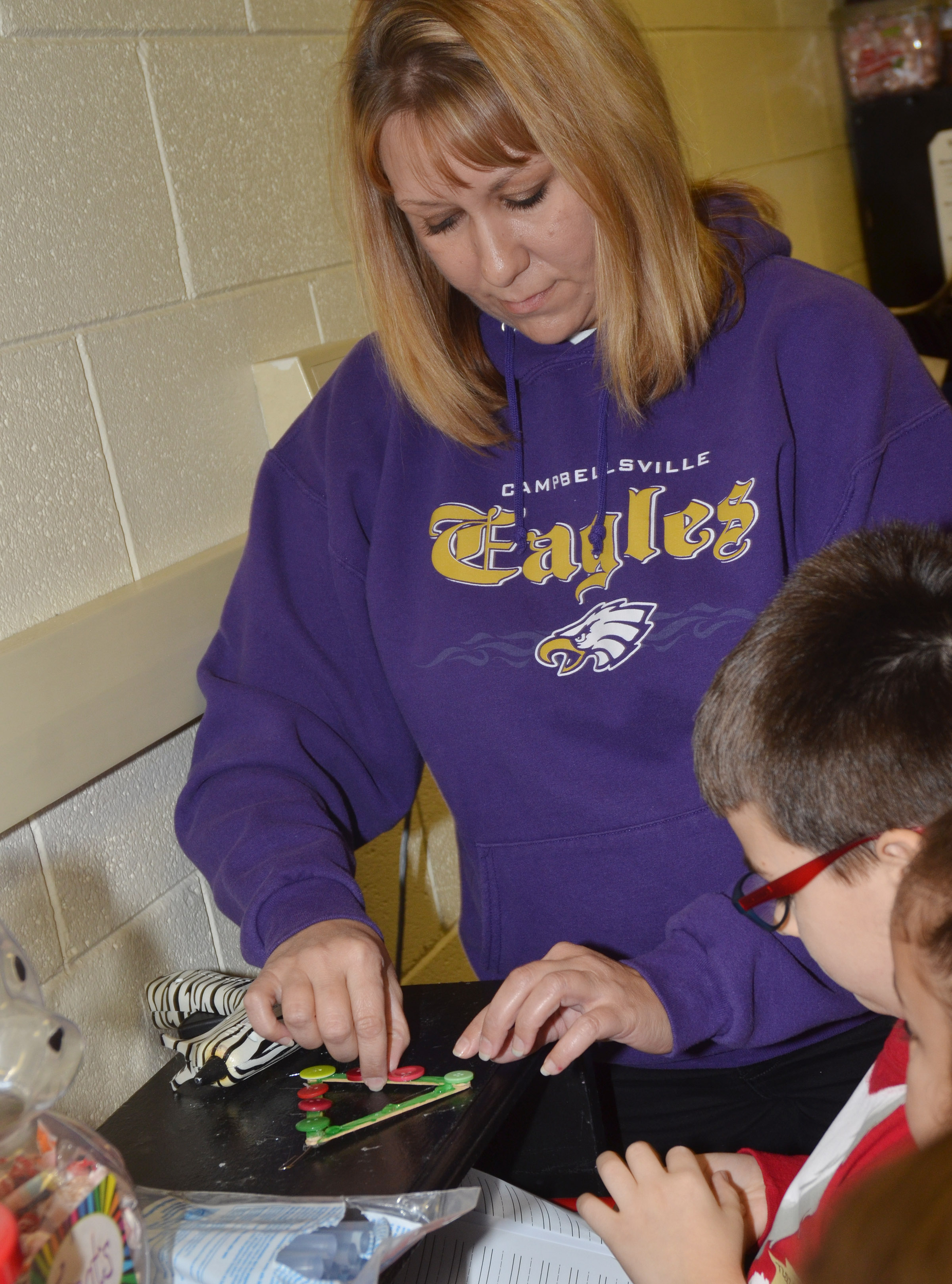 CES first-grade teacher Amanda Greer helps her students make their Christmas tree ornaments.