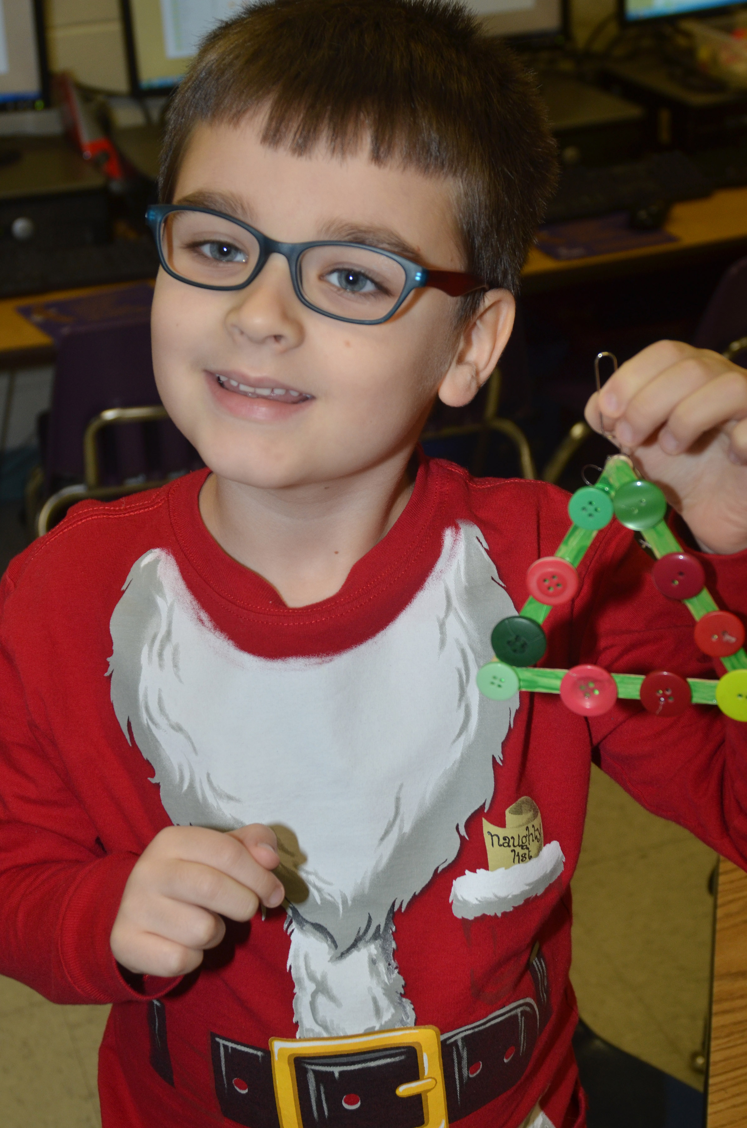 CES first-grader Sawyer Lange holds his finished Christmas tree ornament.
