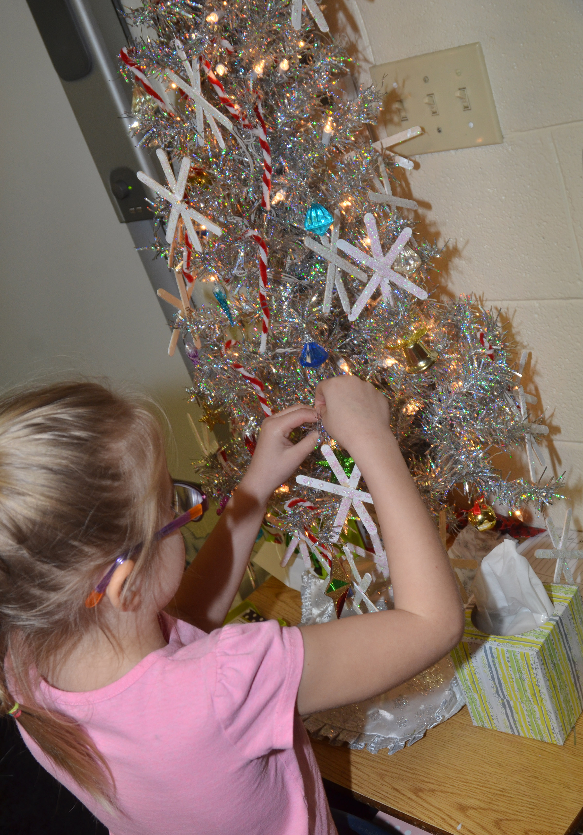 CES first-grader Jaden Lutz places her snowflake ornament on the class Christmas tree.