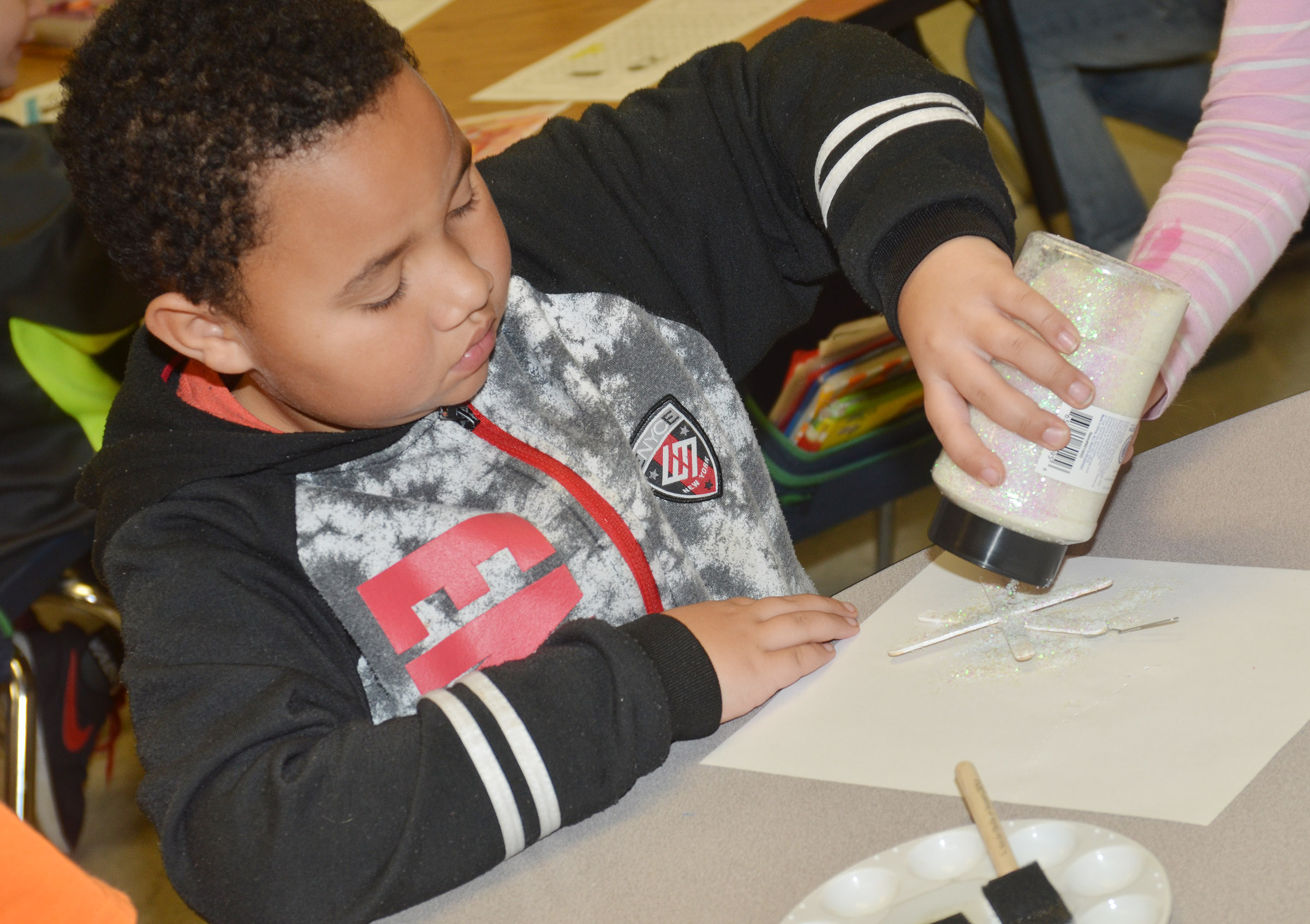 CES first-grader Justin Walls adds glitter to his snowflake ornament.