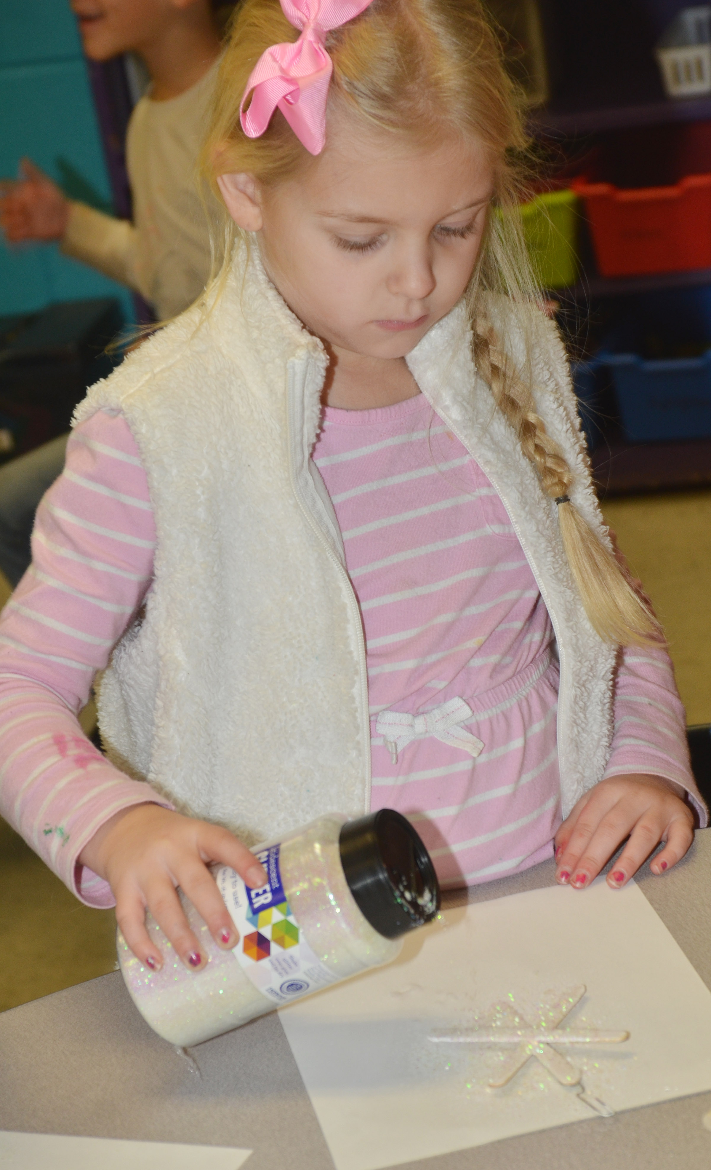 CES first-grader Aubrey Novak adds glitter to her snowflake ornament.