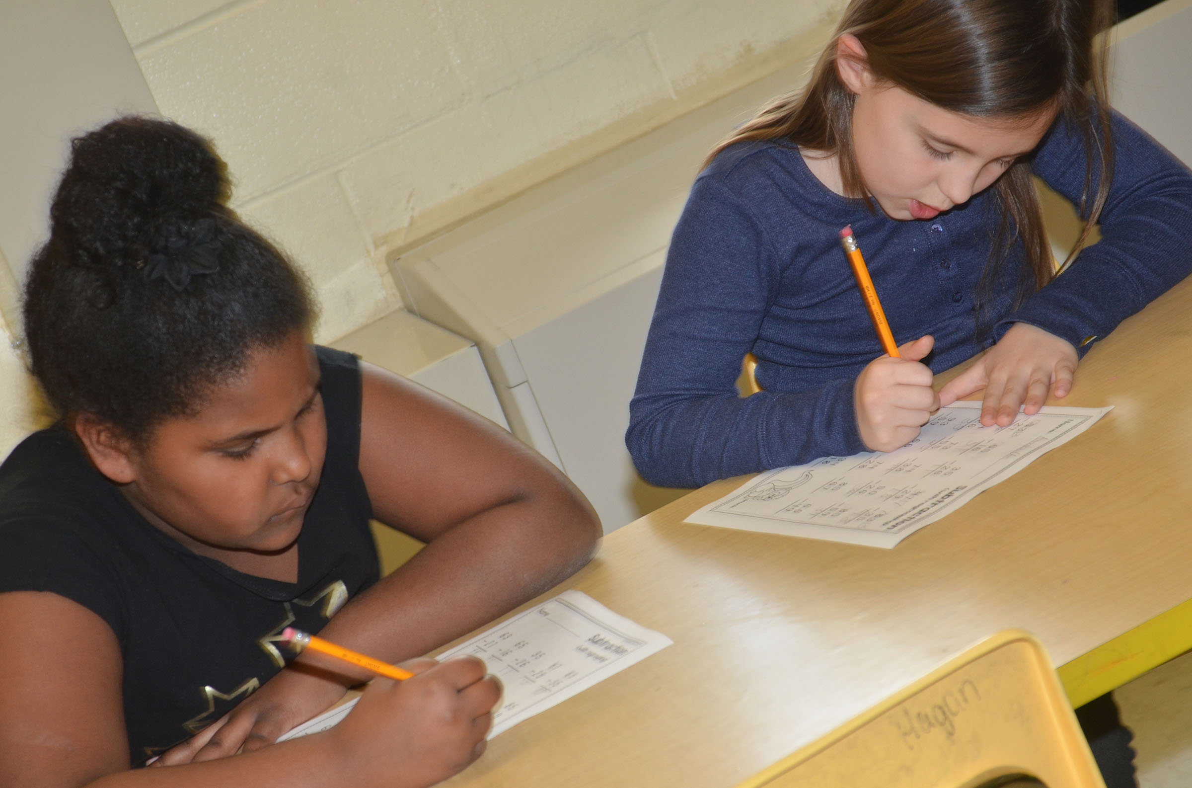 CES second-graders Ajada Smith, at left, and Annabelle Brockman work subtraction problems.