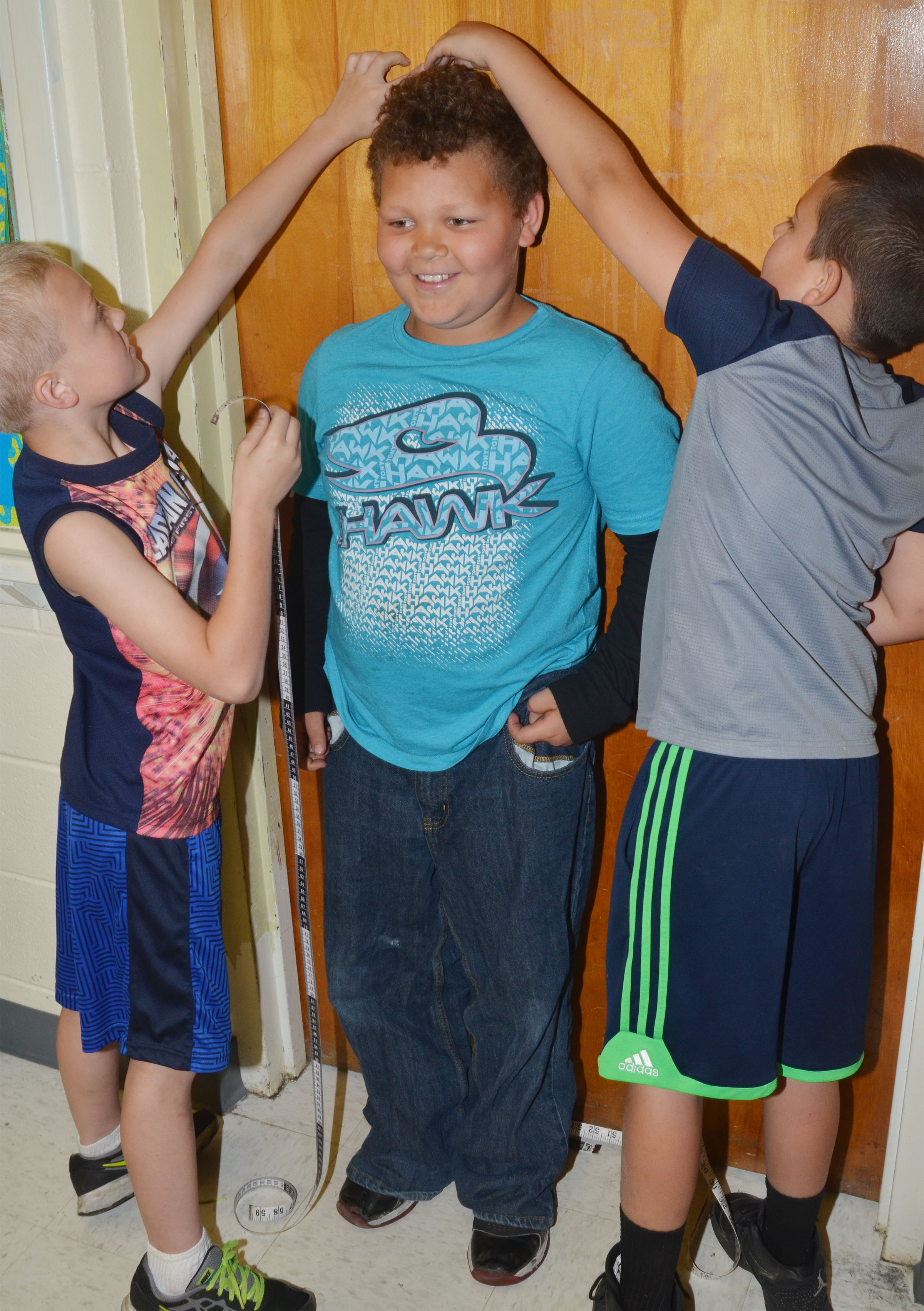 CES second-grader Drevonte Gurley stands tall as his classmates Trenton Harris, at left, and Damien Clark measure him.