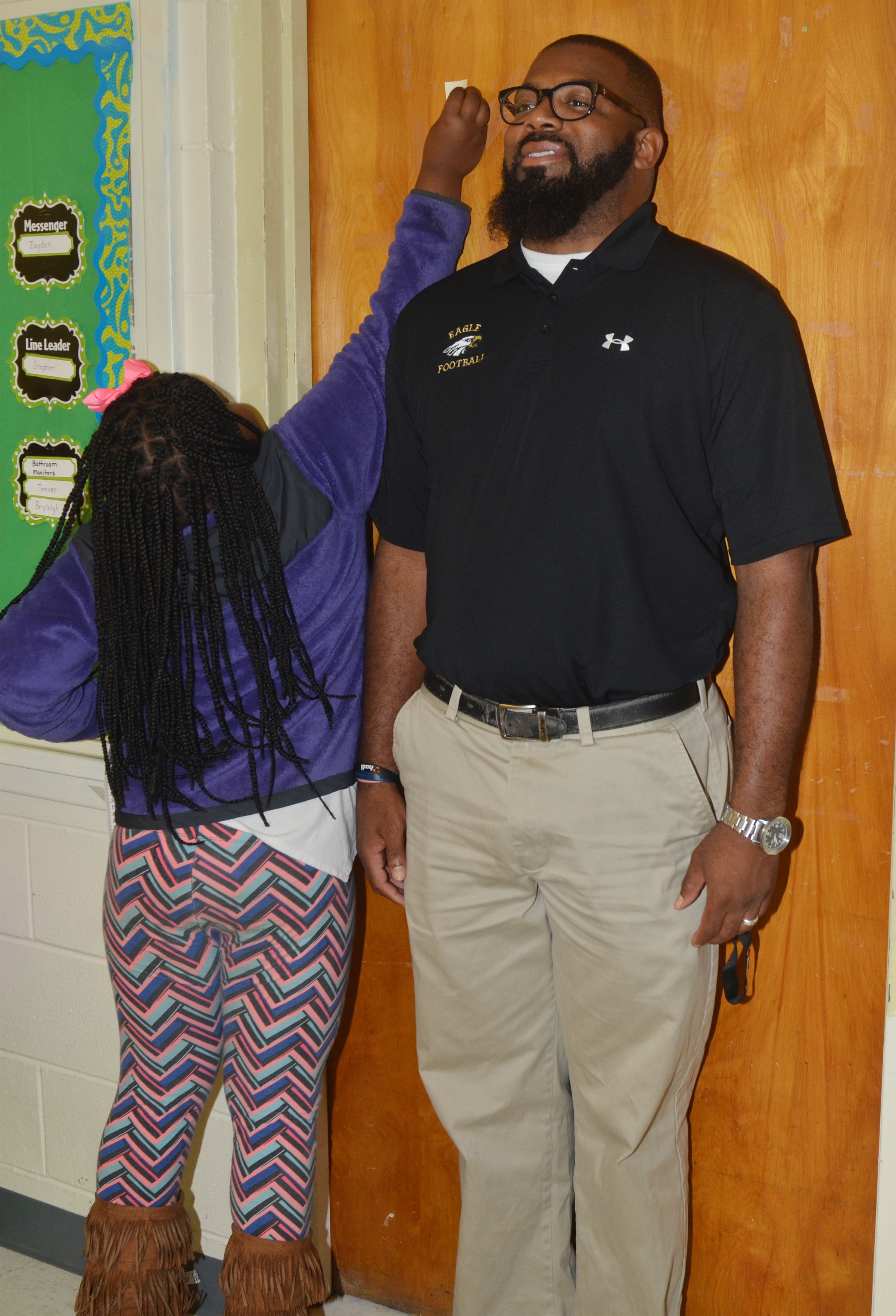 CES second-grader Ajada Smith measures Will Griffin, an exceptional child educator at CES, to see his height.