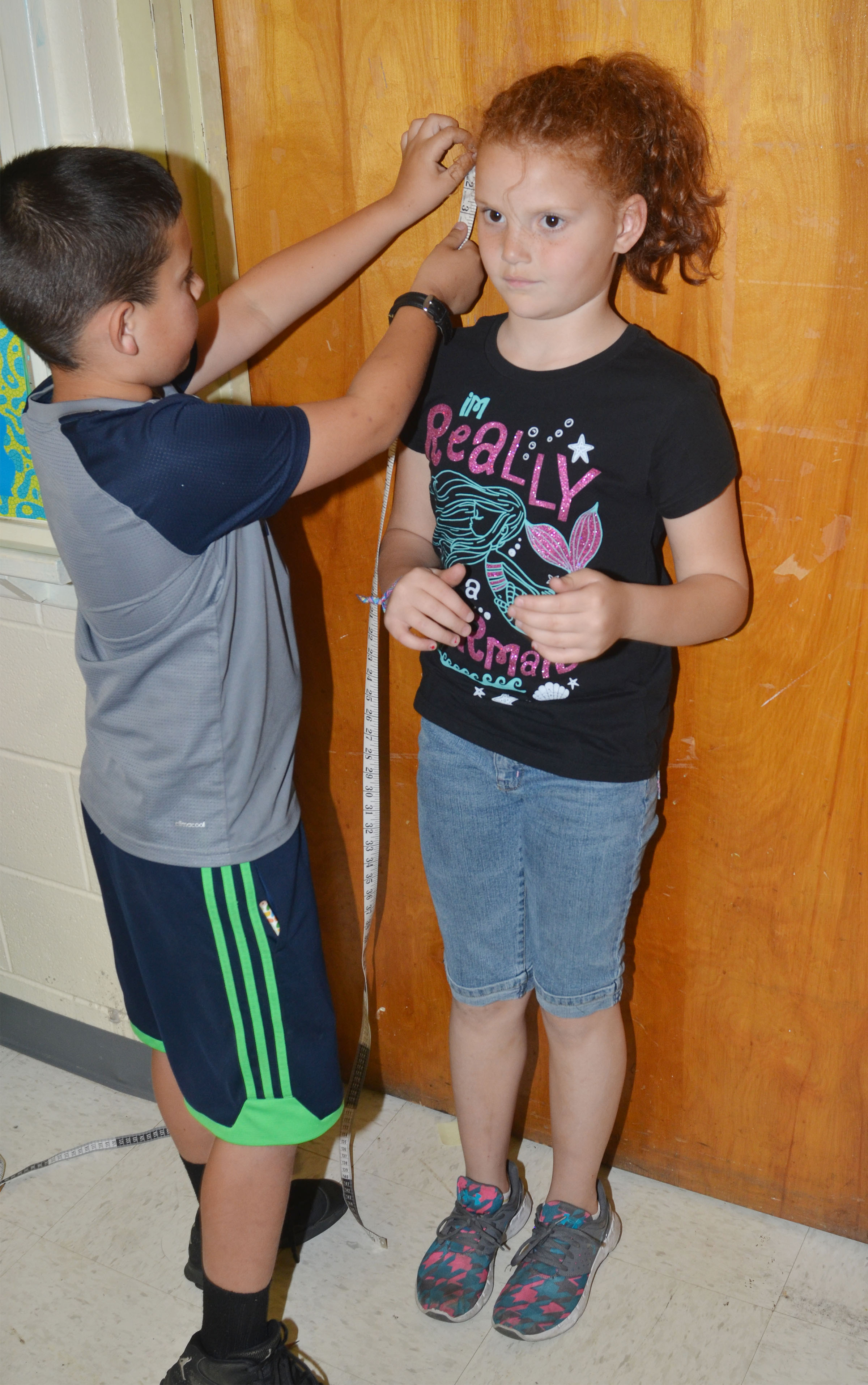 CES second-grader Damien Clark measures Analeigh Foster.
