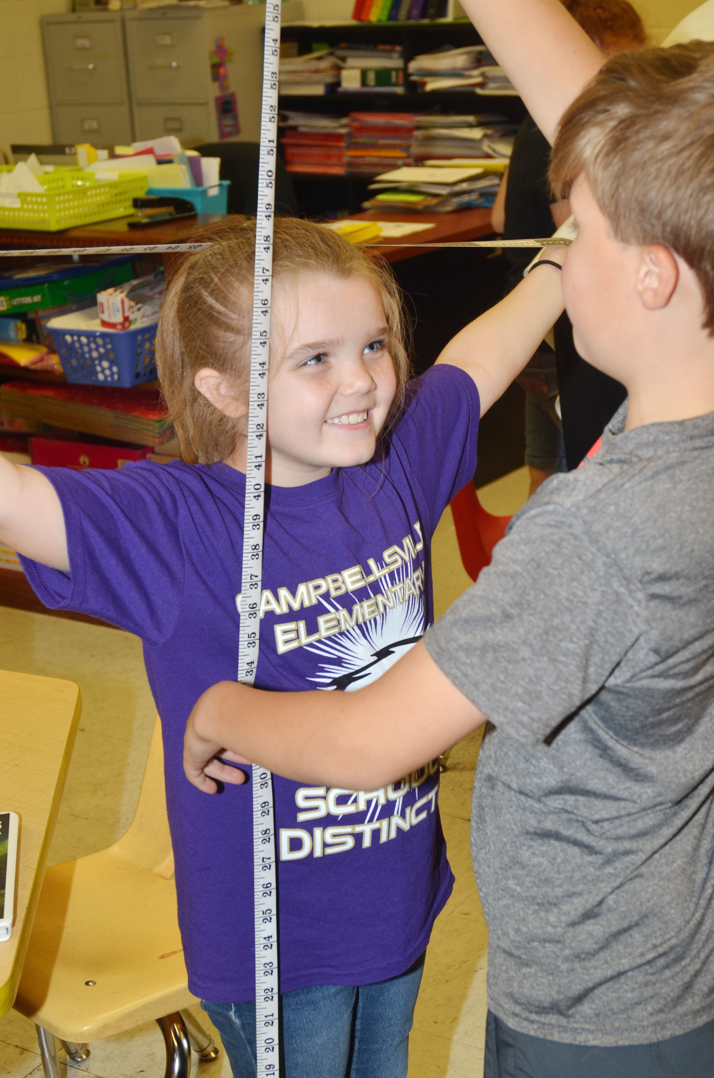 CES second-grader Jaylin Christie smiles as classmate Emerson Gowin measures her.