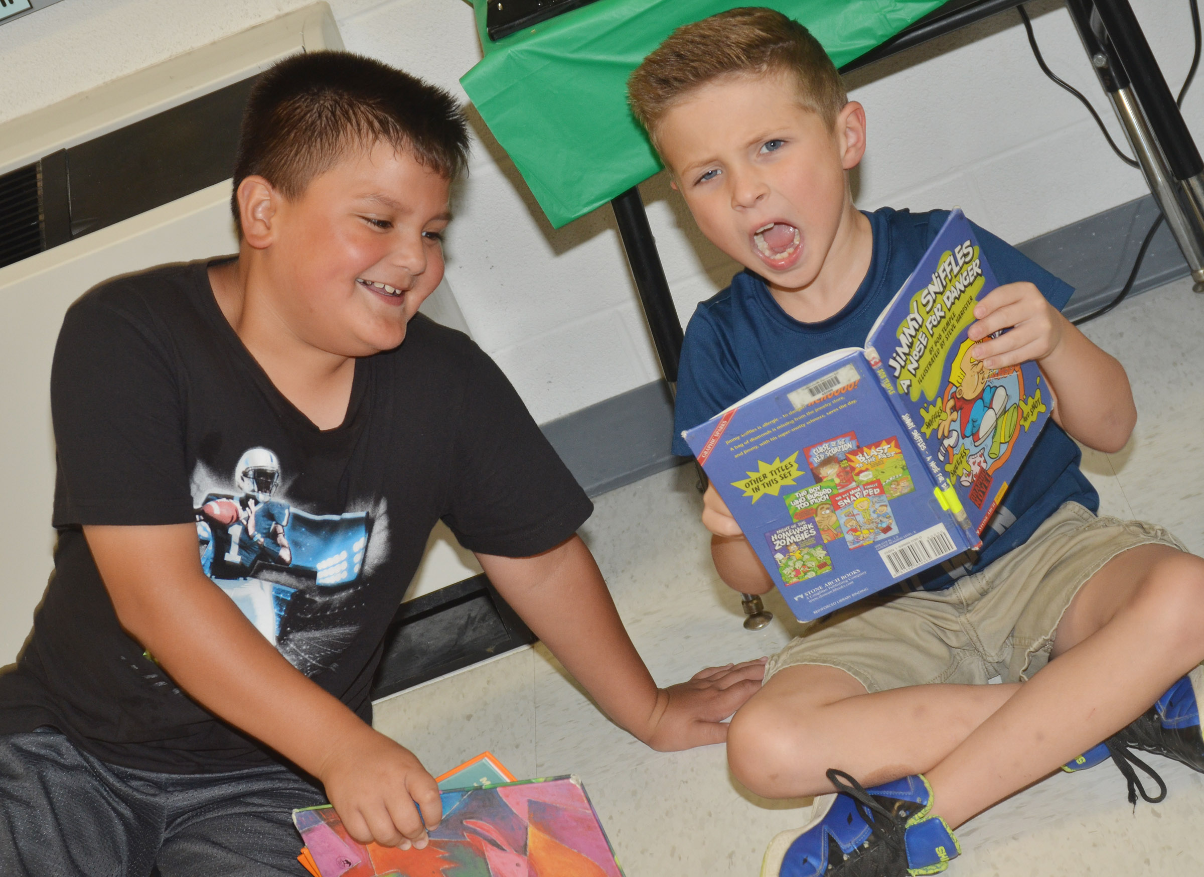CES second-graders Eric Mixtega, at left, and Bryson Gabehart have fun reading a book together.