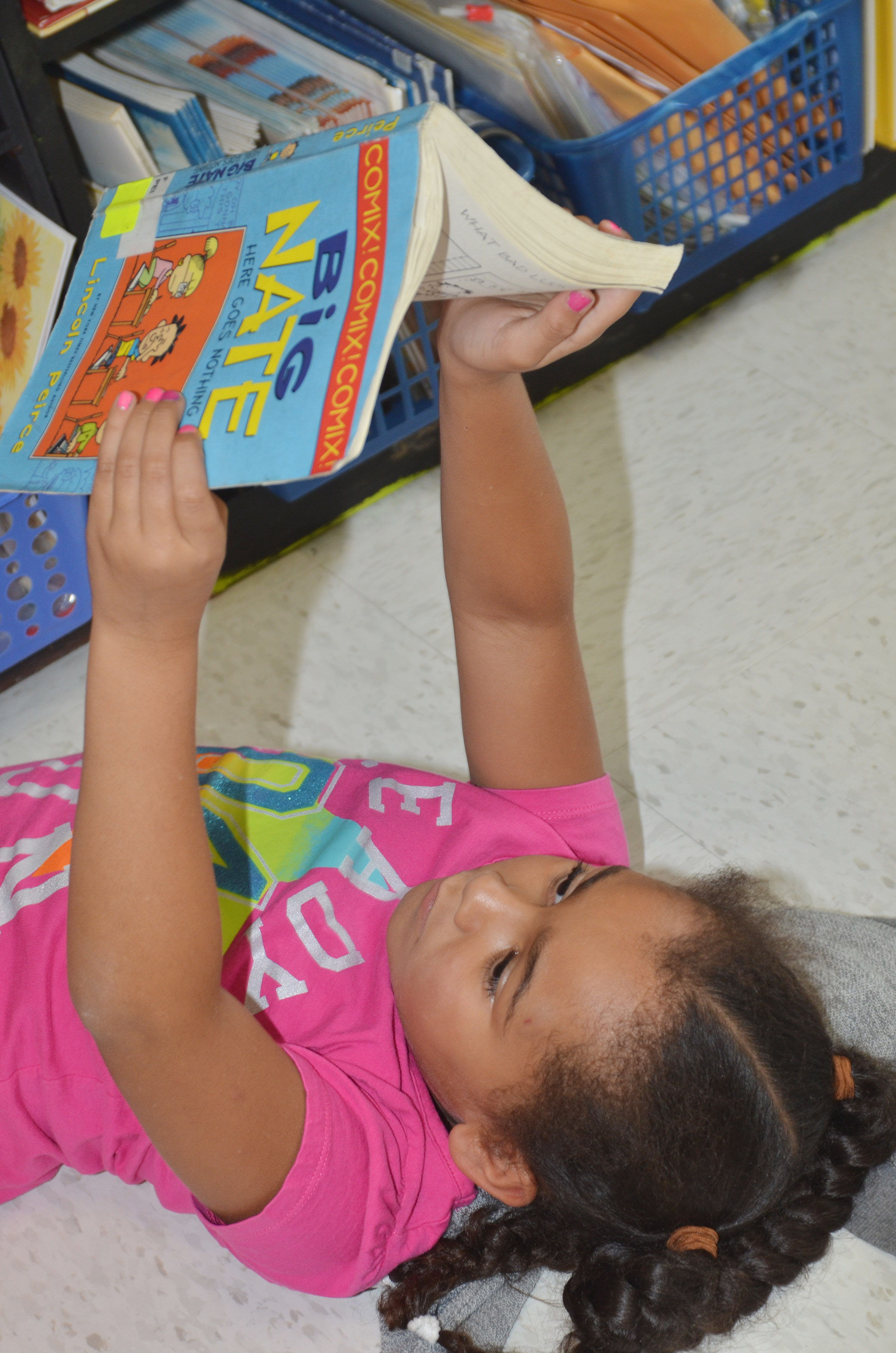 CES second-grader Keitona Whitehead lays down to read.