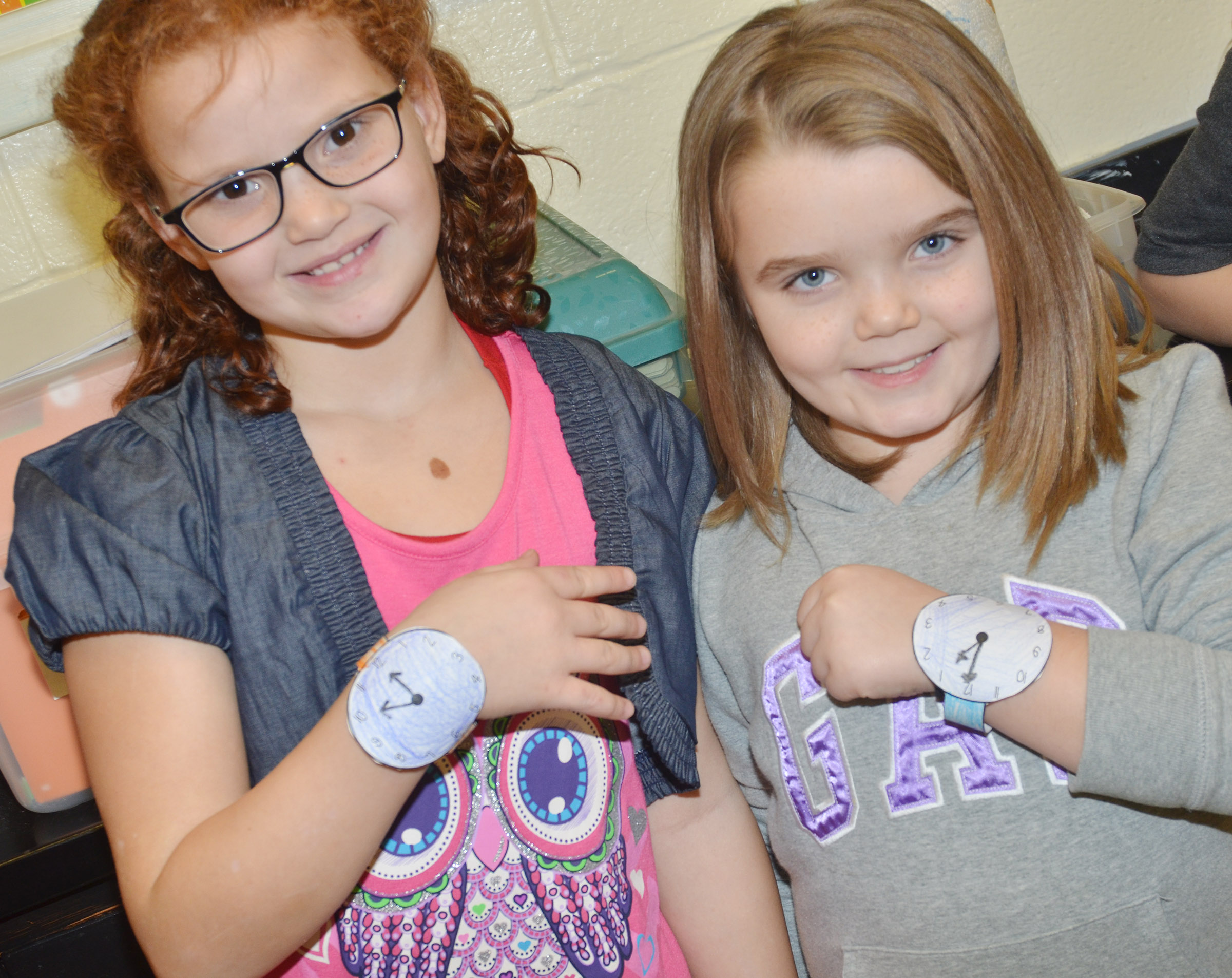 CES second-graders Analeigh Foster, at left, and Jaylin Christie model their watches.