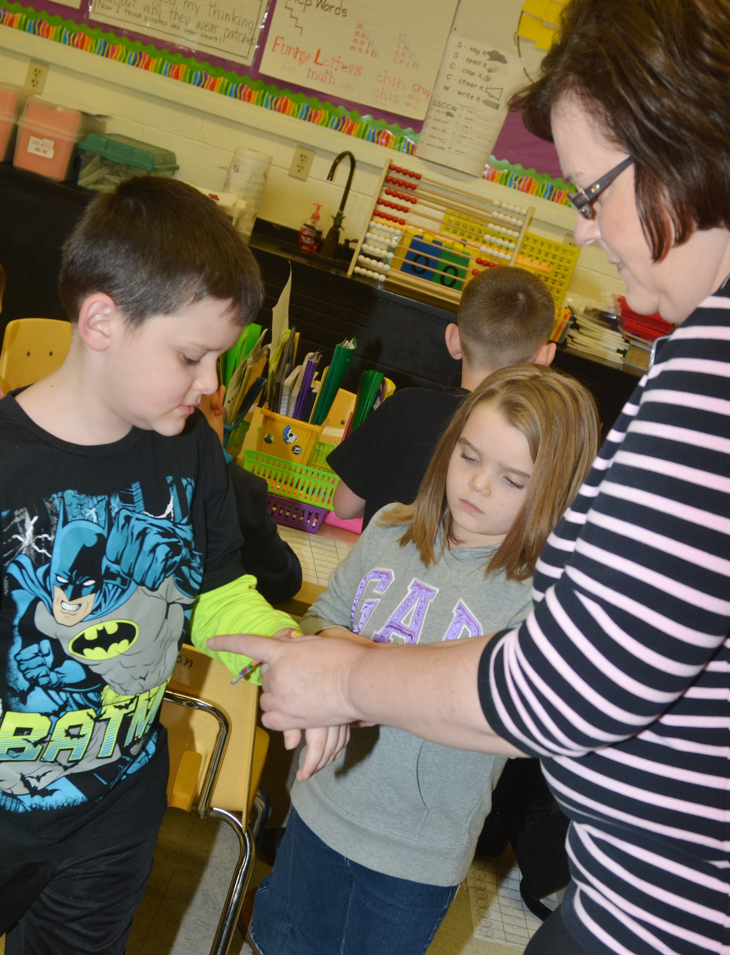 CES second-grade teacher Tonya Hagan helps Weston Veltman fasten his watch, as Jaylin Christie waits her turn.