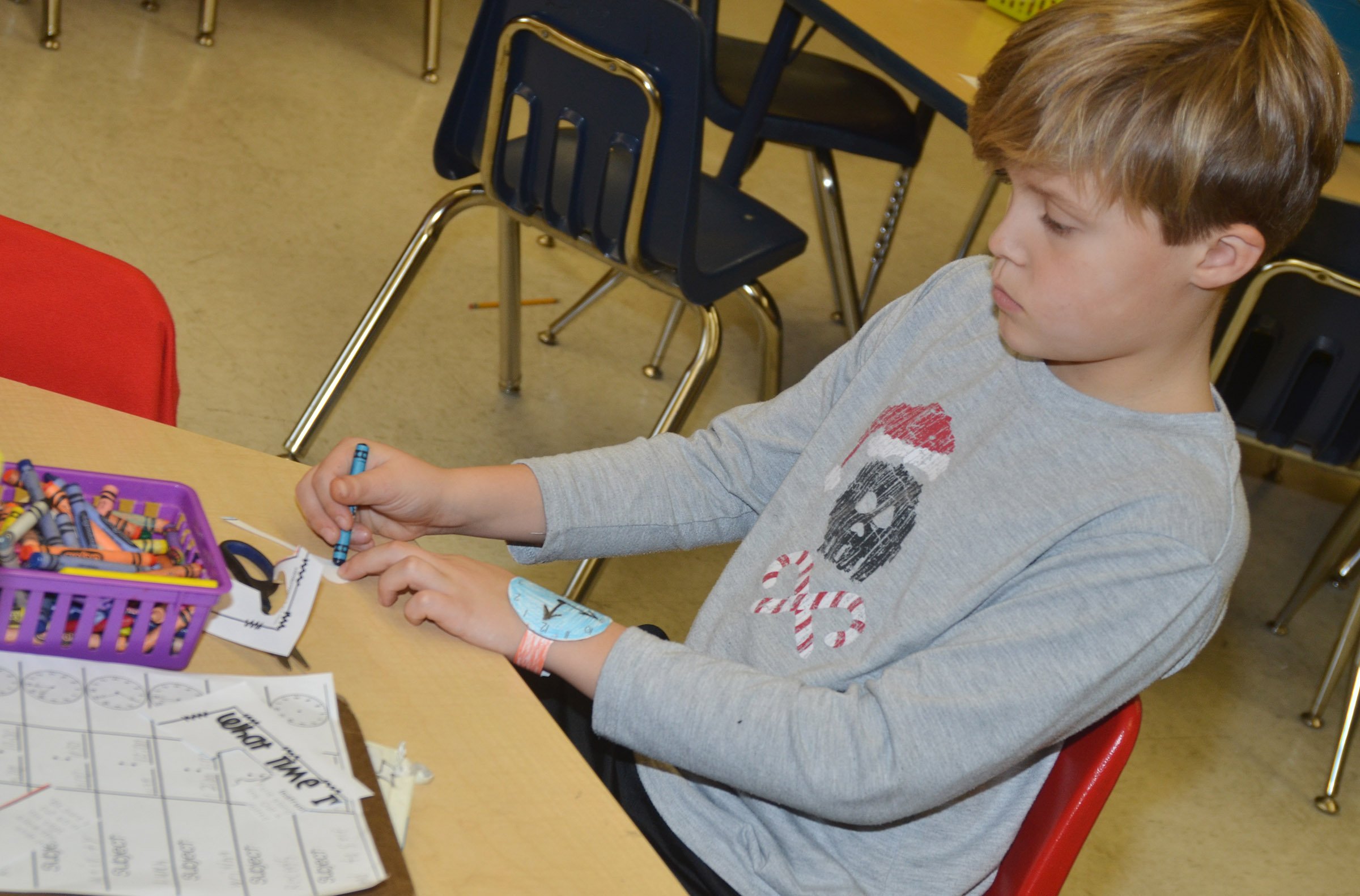 CES second-grader Emerson Gowin wears his watch as he colors.